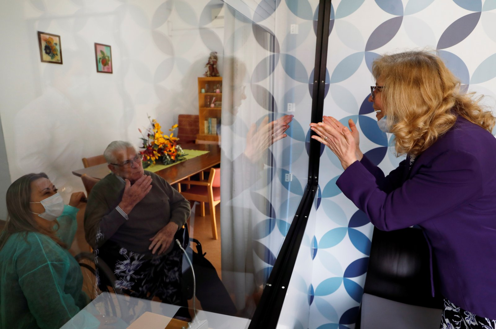 Maria das Merces speaks with her father Adriano Borges through a glass window to prevent infection at an elderly residence as the spread of the coronavirus disease continues, Montijo, Portugal, May 12, 2020.