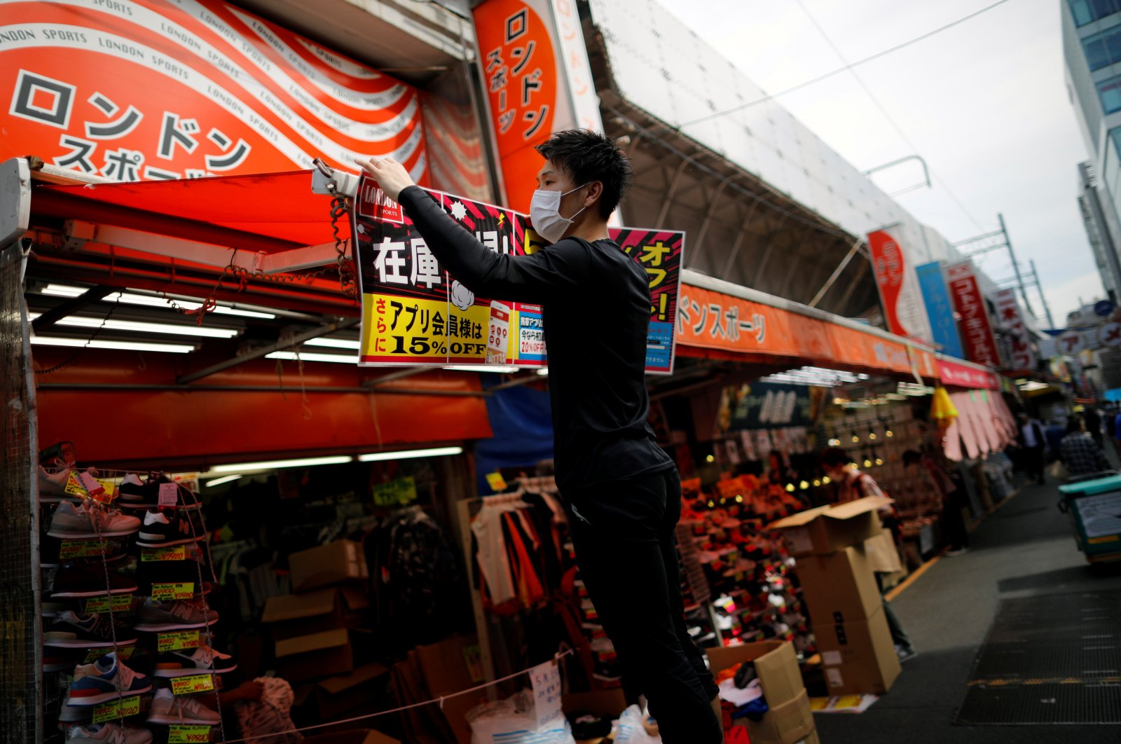 An employee of a shoe shop prepares to reopen the business during the spread of the coronavirus in Tokyo, Japan, May 14, 2020. (Reuters Photo)