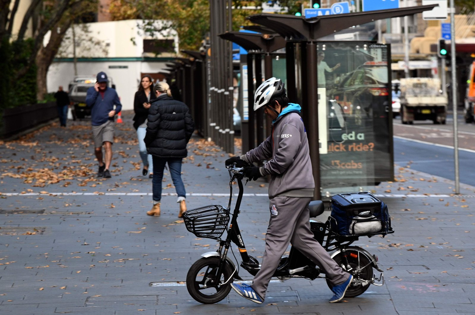 A courier crosses the road to deliver food in the central business district in Sydney, Australia, May 14, 2020. (AFP Photo)