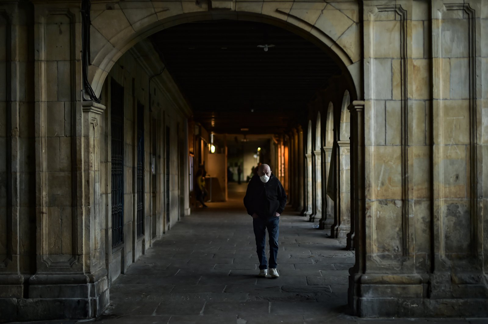 An elderly man wearing face mask to protect against coronavirus walks along ancient porch of the old city, in Pamplona, northern Spain, Wednesday, May 13, 2020. (AP Photo)