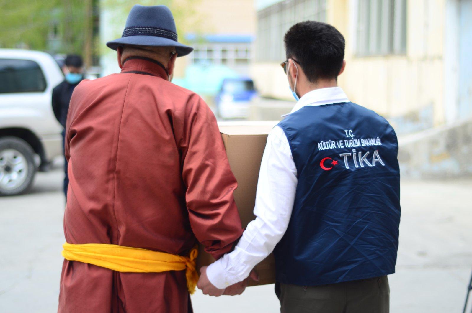 A TIKA volunteer helps a man carry an aid box in Ulaanbaatar, Mongolia, May 12, 2020. (AA Photo)