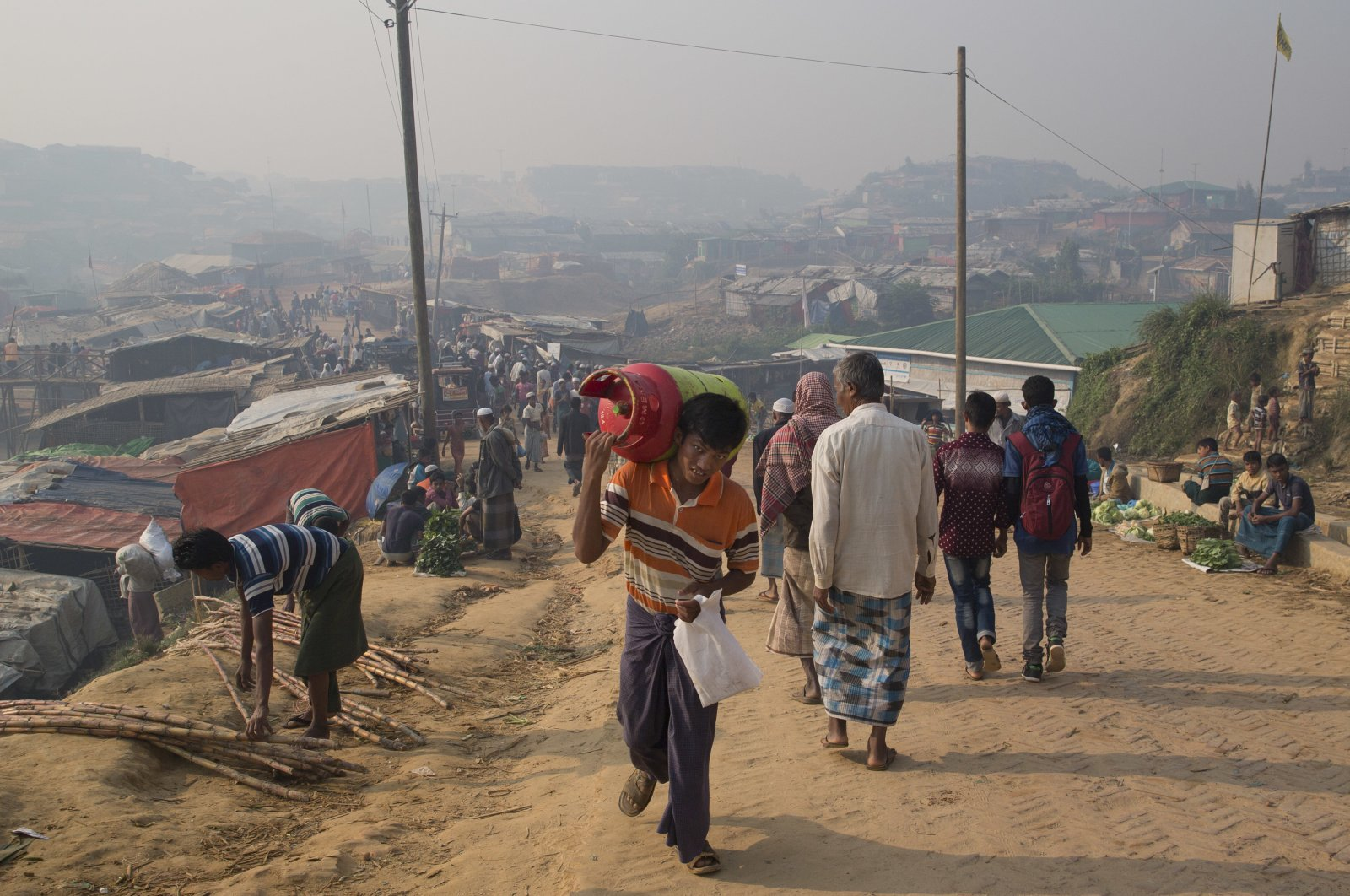 A Rohingya refugee walks carrying a cooking gas cylinder inside Balukhali refugee camp near Cox's Bazaar, Nov. 17, 2018. (AP Photo)