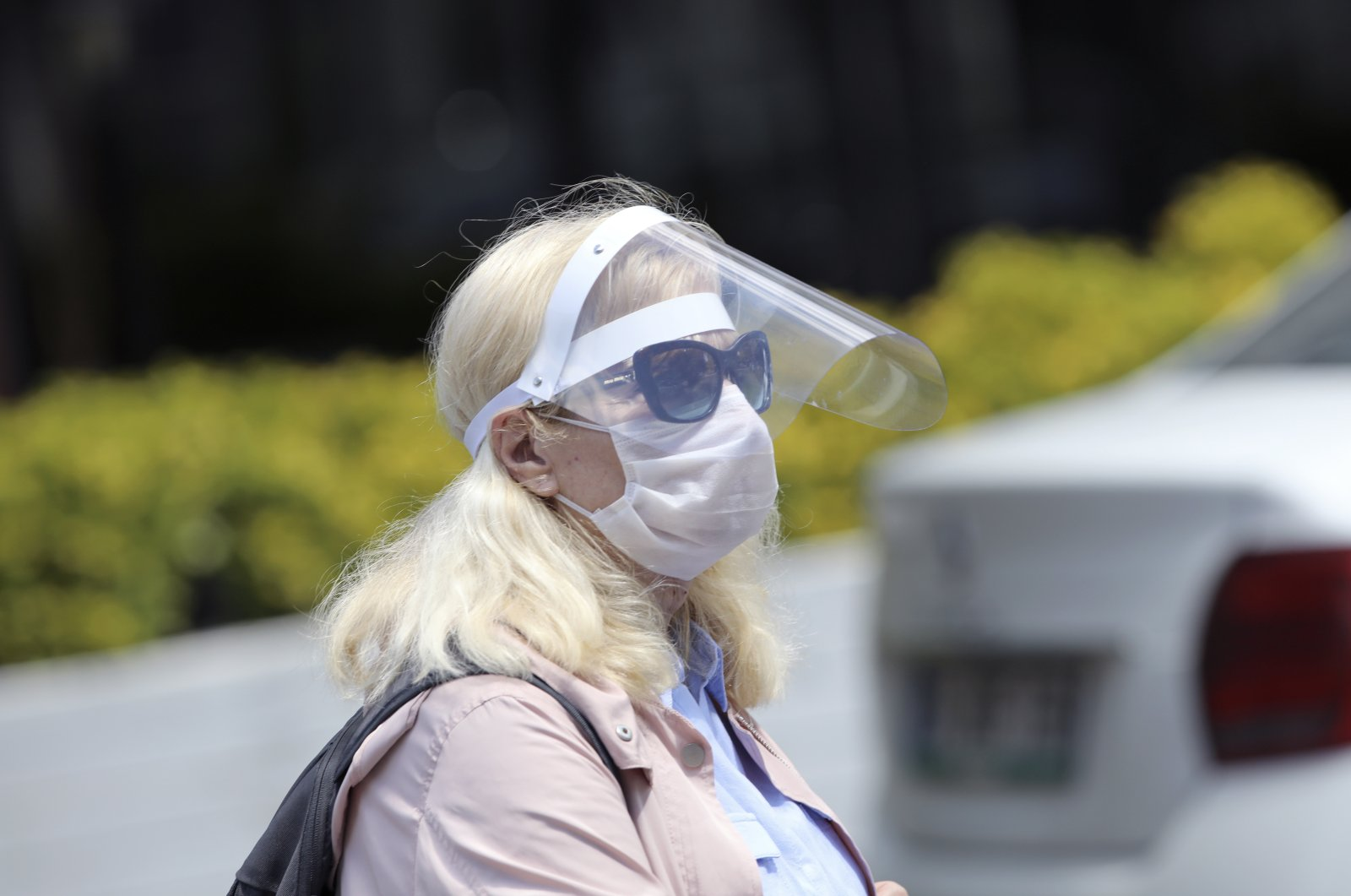 A woman wearing a face shield and mask walks in a local park in Ankara, Turkey, May 10, 2020. (AP Photo)