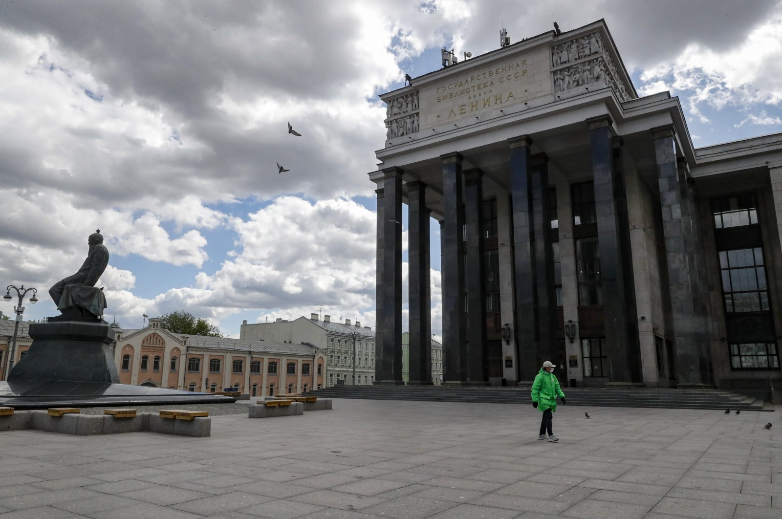 A man wearing a face mask walks in front of the Russian State Library, Moscow, May 13, 2020. (EPA Photo)