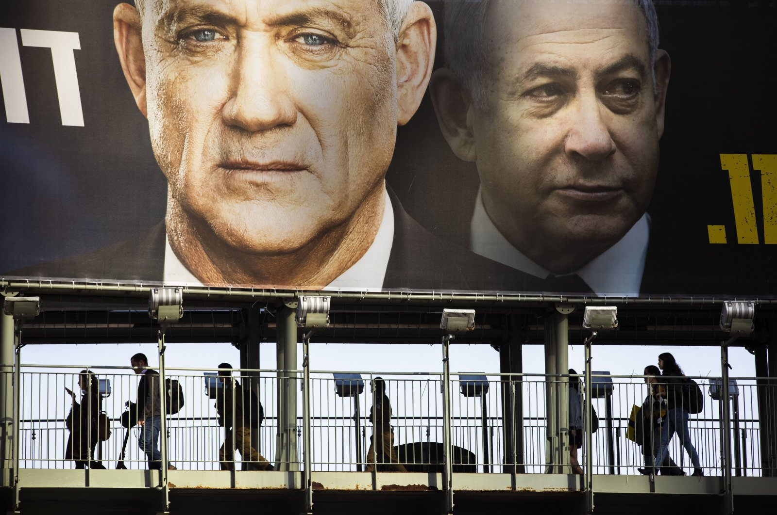 People walk on a bridge under an election campaign billboard for the Blue and White party, then an opposition party led by Benny Gantz, left, and showing Israeli Prime Minister Benjamin Netanyahu, Ramat Gan, Israel, Feb. 18, 2020. (AP Photo)