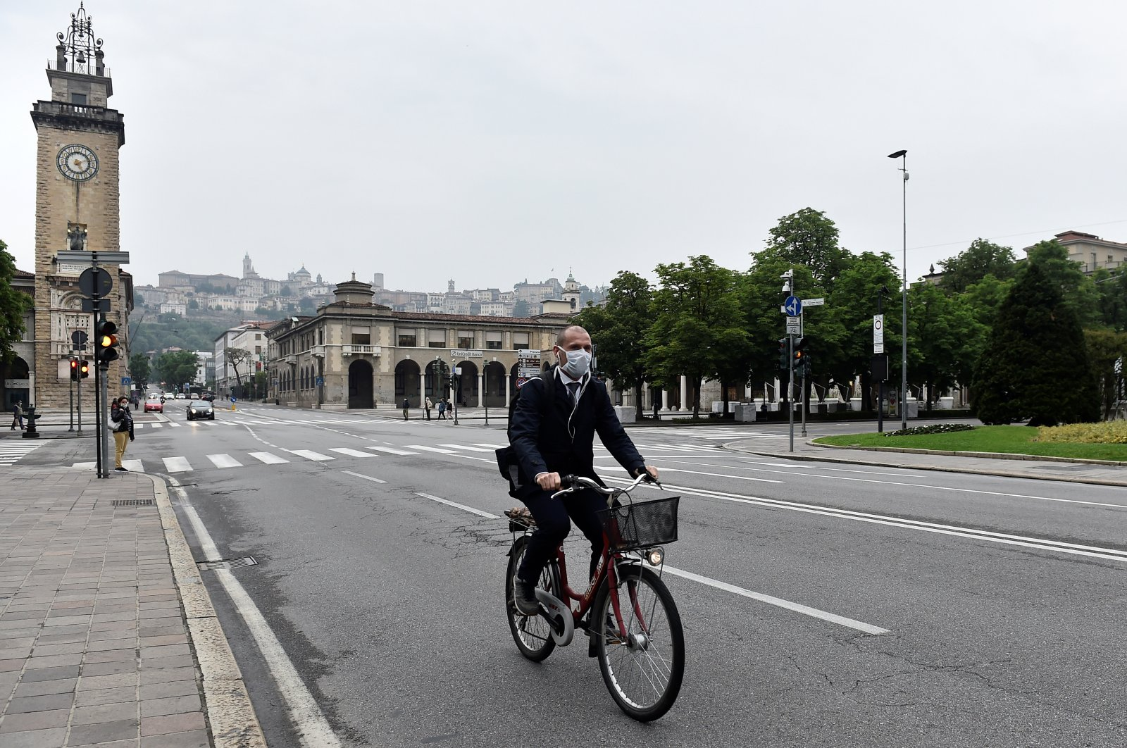 A man wearing a face mask rides a bicycle, Bergamo, Italy, May 13, 2020. (REUTERS Photo)