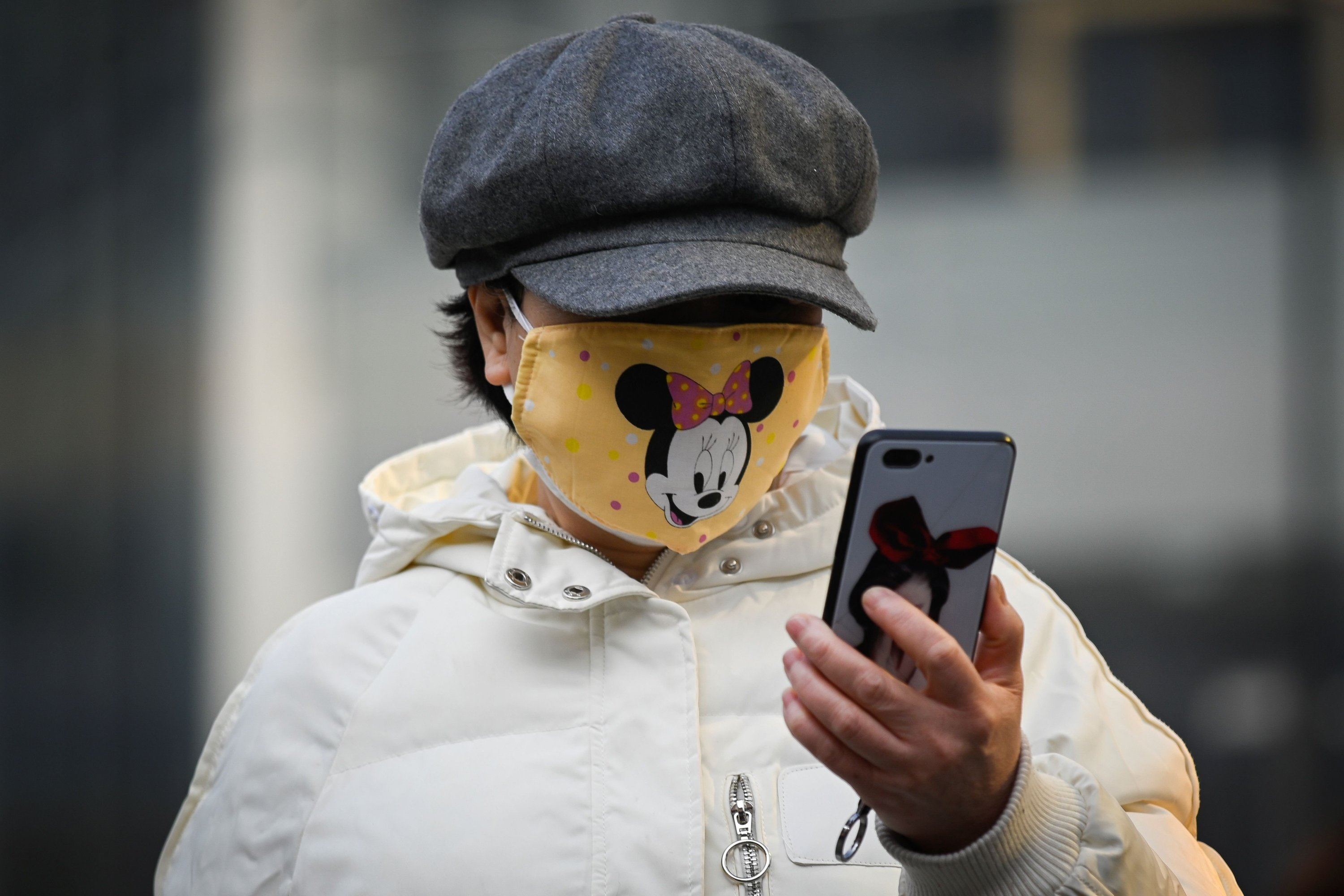 A woman wearing a Minnie Mouse face mask looks at her mobile phone in Beijing on February 11, 2020. (AFP Photo)