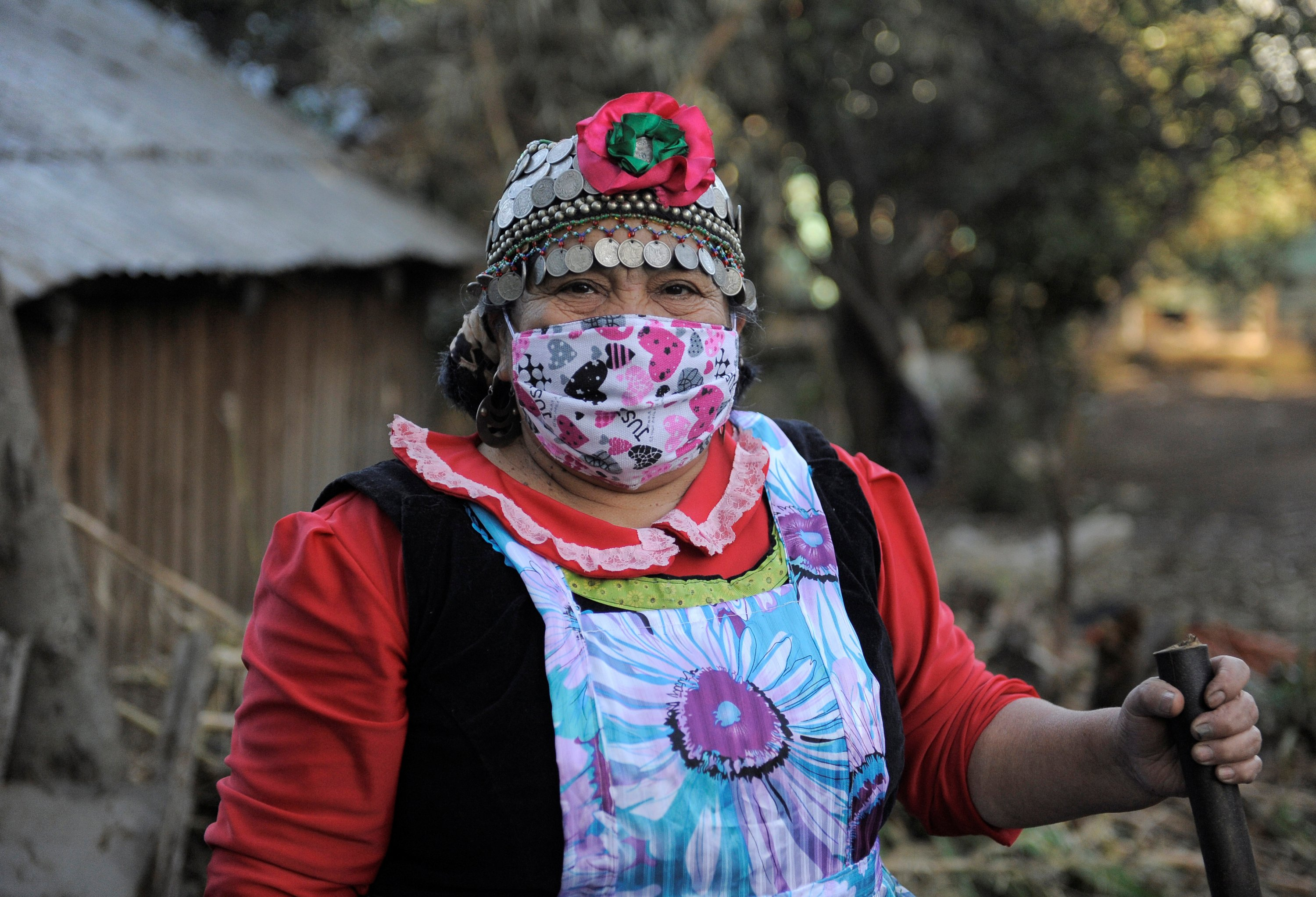 Estela Astorga Porma, a Mapuche Indian woman, wears a face mask while posing for a picture outside her 'Ruka' (House) while they self-isolate in Huentelolen area close Tirua town, Chile, May 7, 2020. (Reuters Photo)