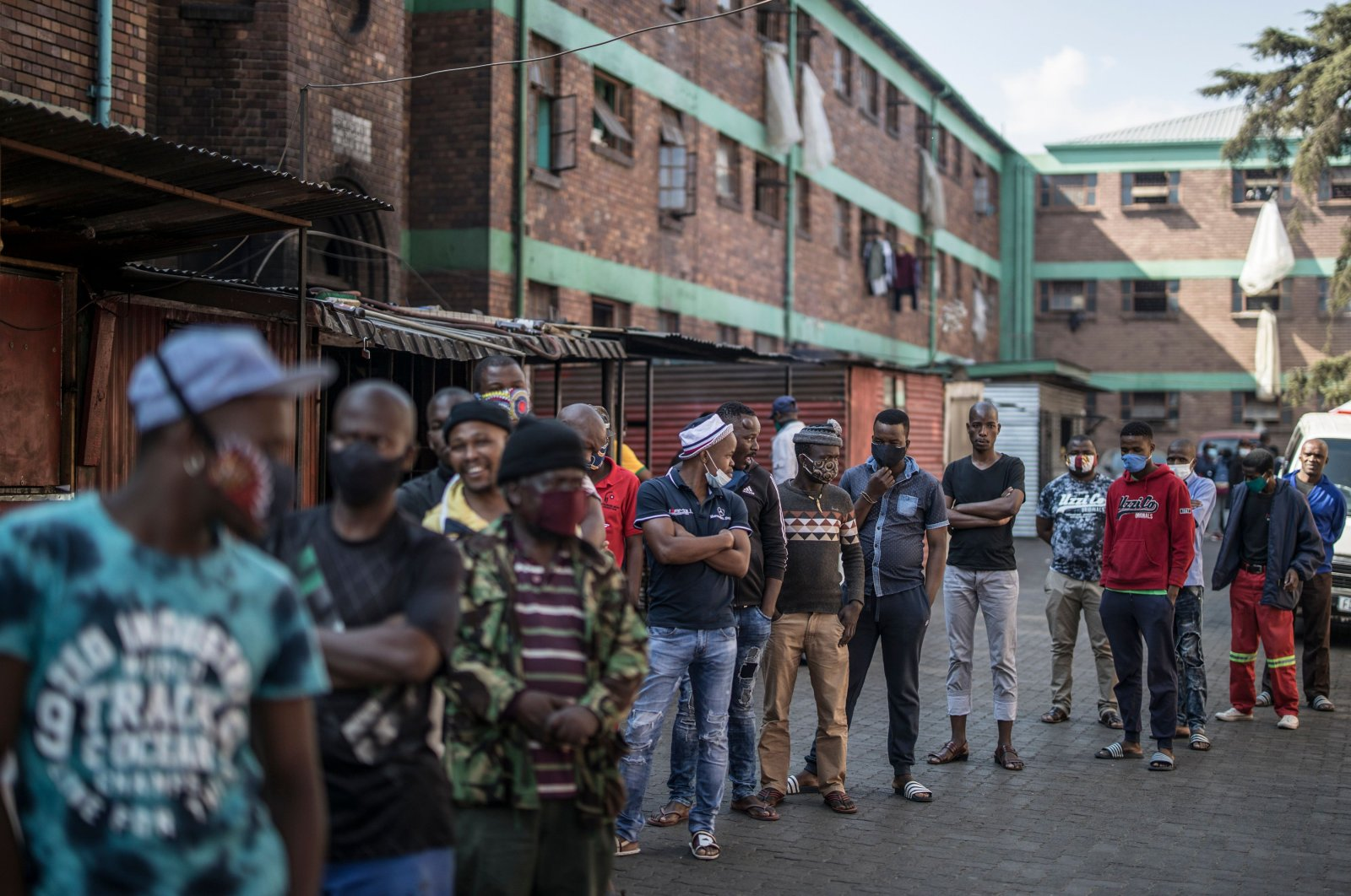 Men line up as Ministry of Health workers conduct a coronavirus screening and testing drive at the Wolhuter men's hostel in the Jeppestown district of Johannesburg, South Africa, May 14, 2020. (AFP Photo)
