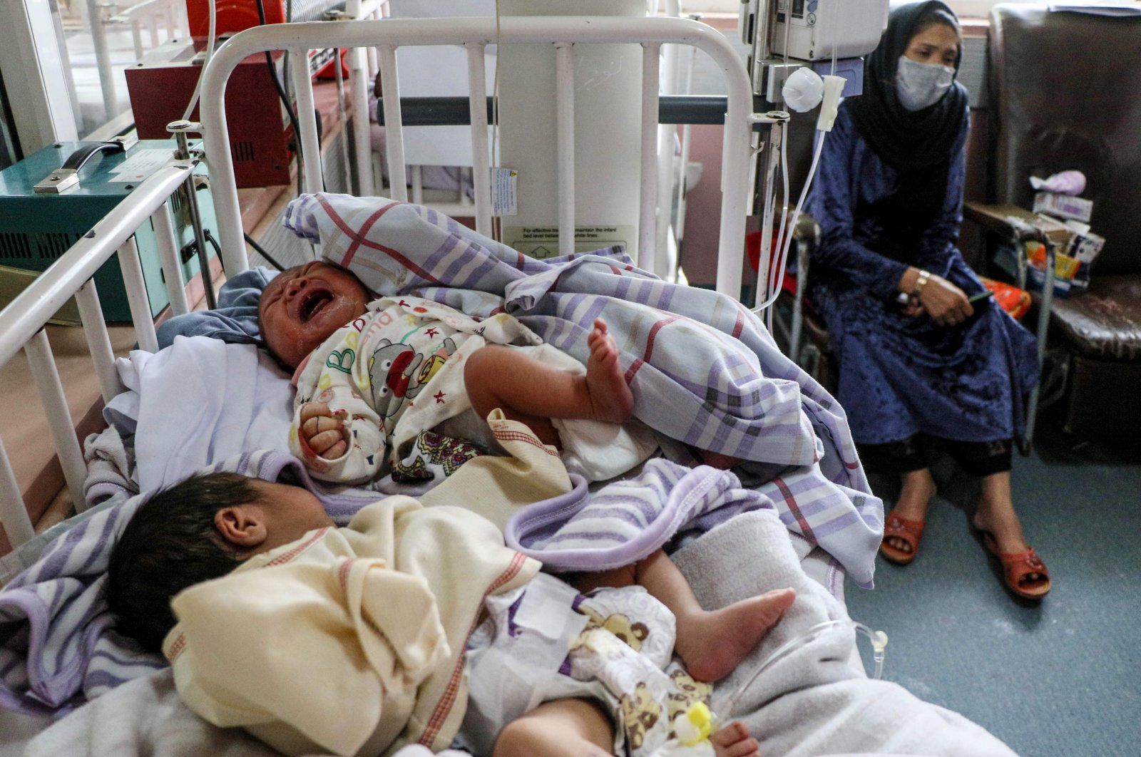 A woman (R) sits next to newborn babies who lost their mothers following a suicide attack in a maternity hospital, in Kabul on May 13, 2020. (AFP Photo)