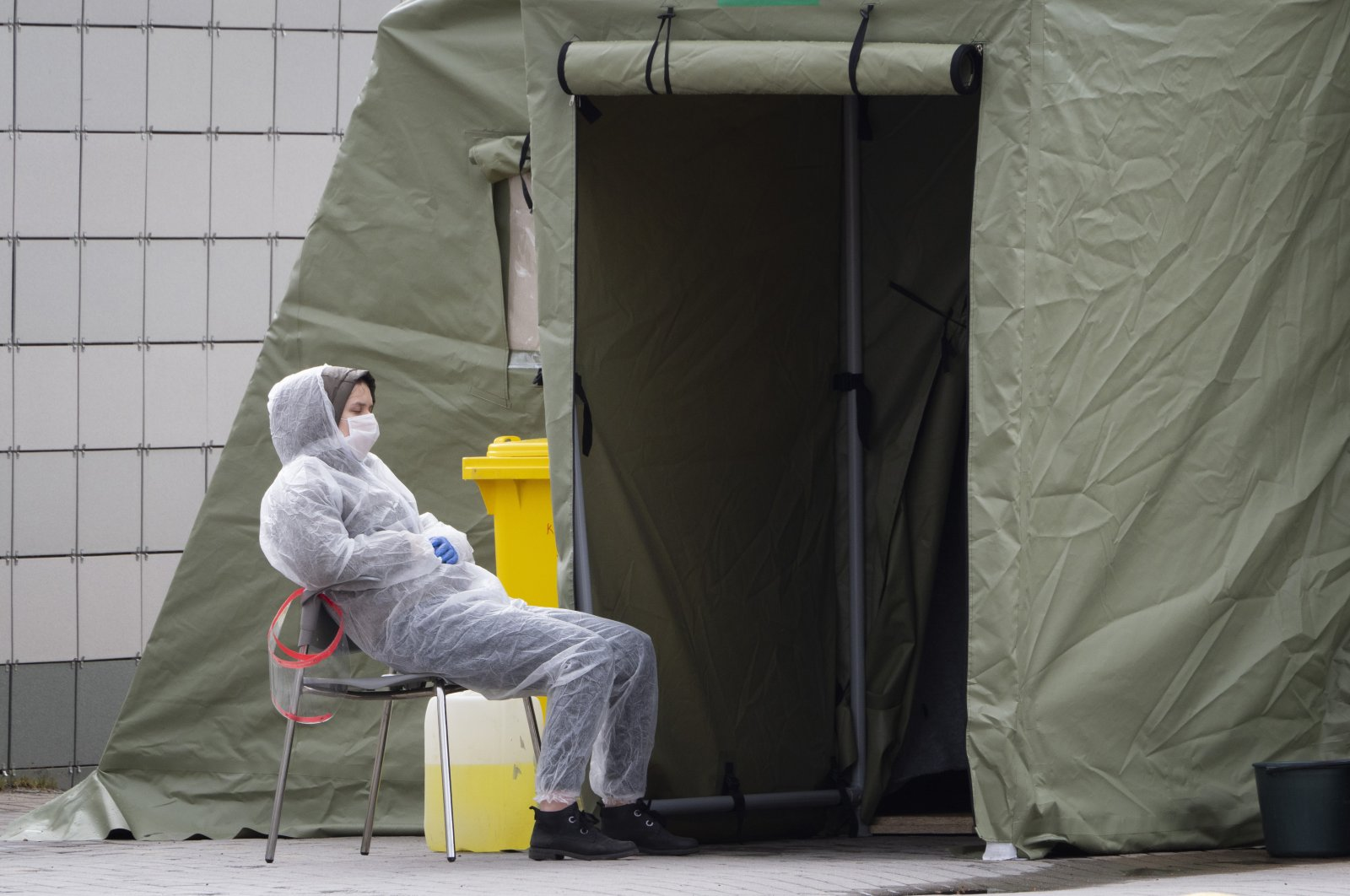A medical worker wearing protective equipment rests in a yard of a hospital specialising in the treatment of patients with the coronavirus in St.Petersburg, Russia, May 14, 2020. (AP Photo)