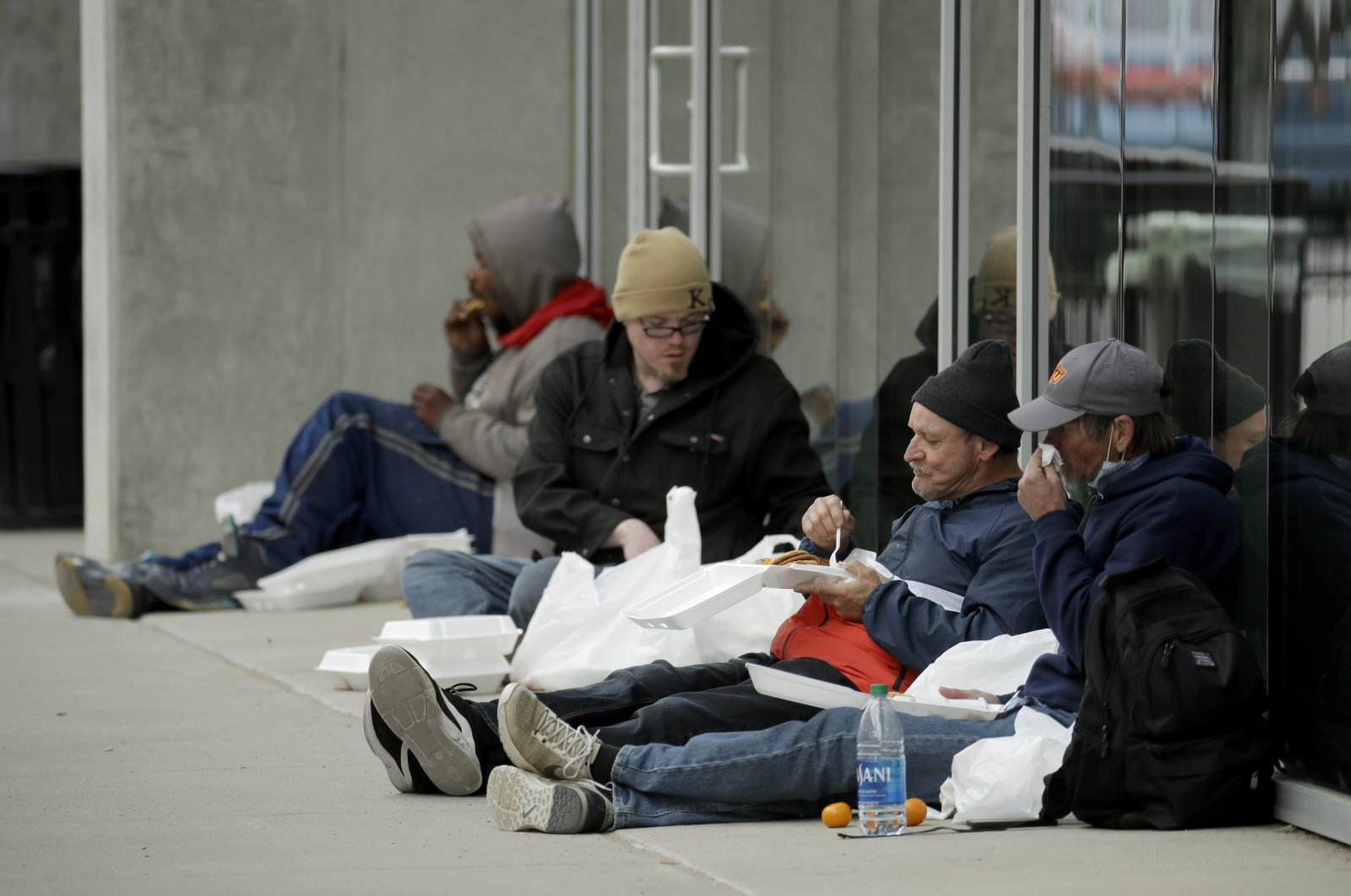 People eat free meals on a downtown sidewalk after picking them up at a nearby restaurant, May 11, 2020, in Kansas City, Missouri. (AP Photo)