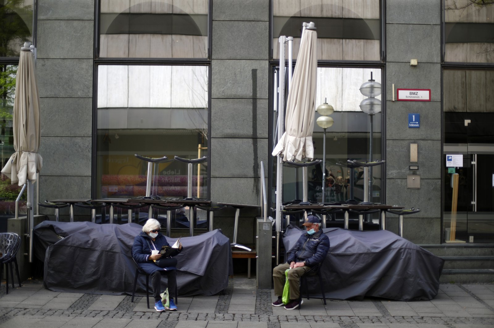 An elderly couple sits outside a closed bar during the lockdown due to the coronavirus outbreak downtown in Munich, Germany, May 9, 2020. (AP Photo)