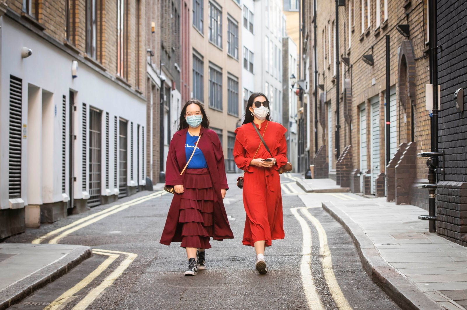 Two Chinese girls wearing masks walk down an empty street in Soho, London, Thursday, May 7, 2020. (PA via Reuters)