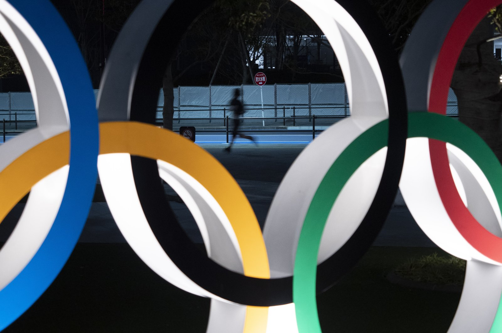 A man jogs past the Olympic rings in Tokyo, March 30, 2020. (AP Photo)