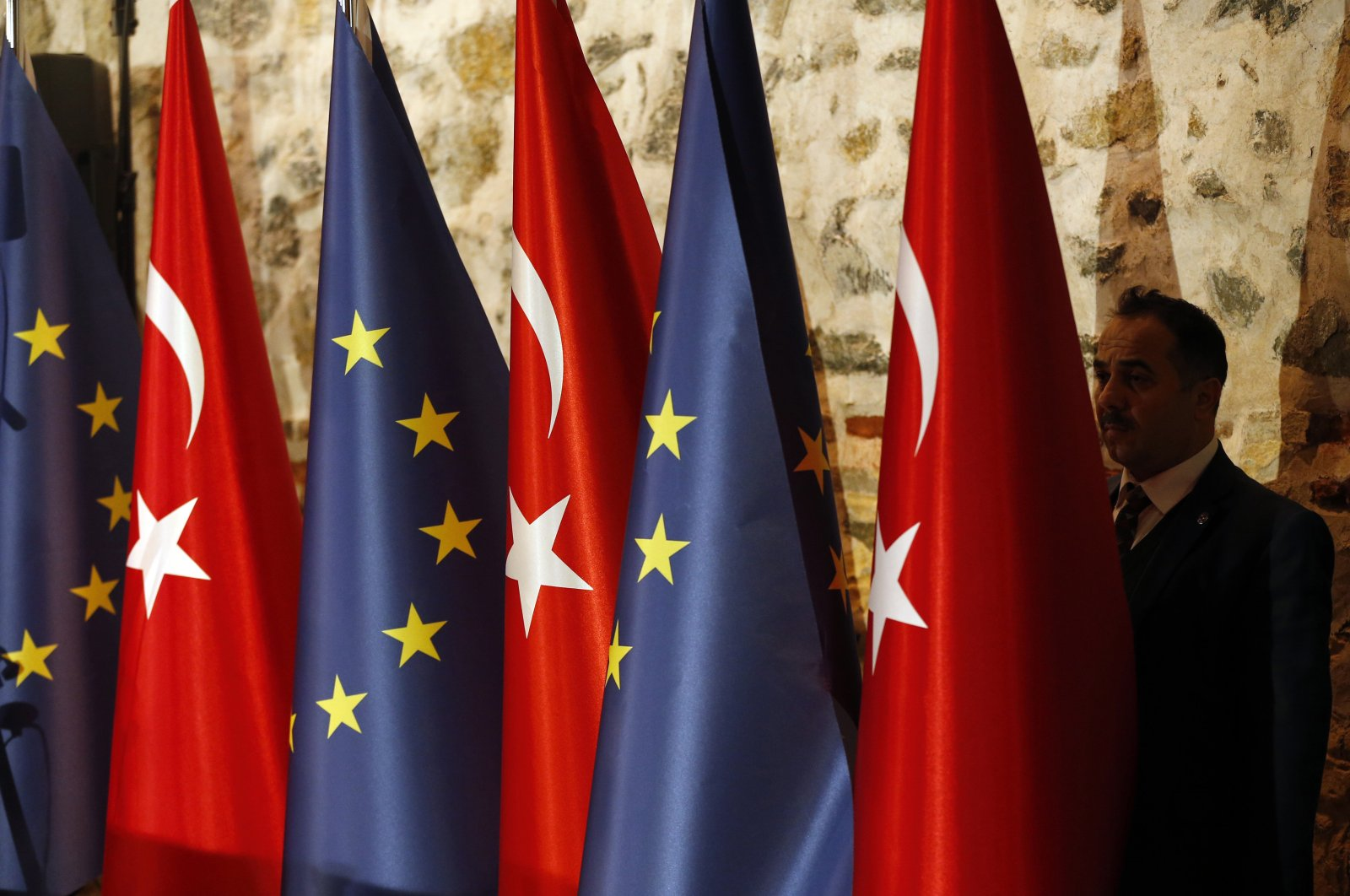 An official adjusts Turkey's and European Union's flags prior to the opening session of a high-level meeting in Istanbul, Feb. 28, 2019. (AP Photo)