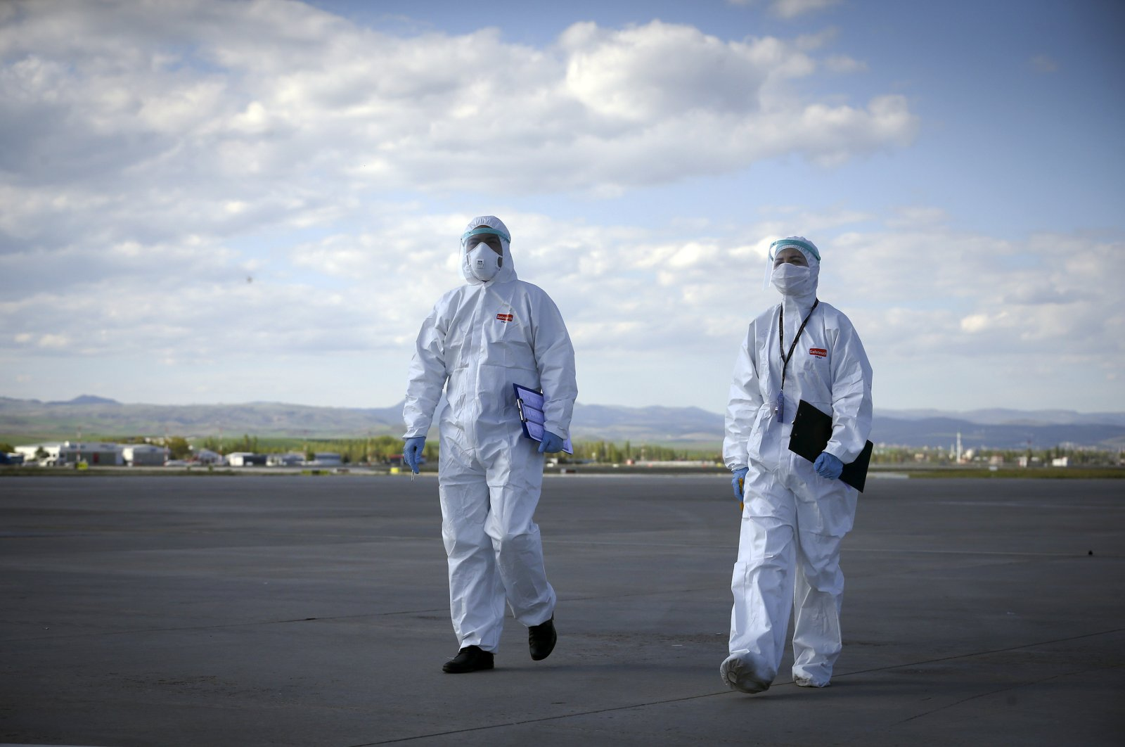 Health workers walk to greet Turkish citizens arriving at Ankara Esenboğa Airport, Ankara, May 10, 2020. (AA Photo)