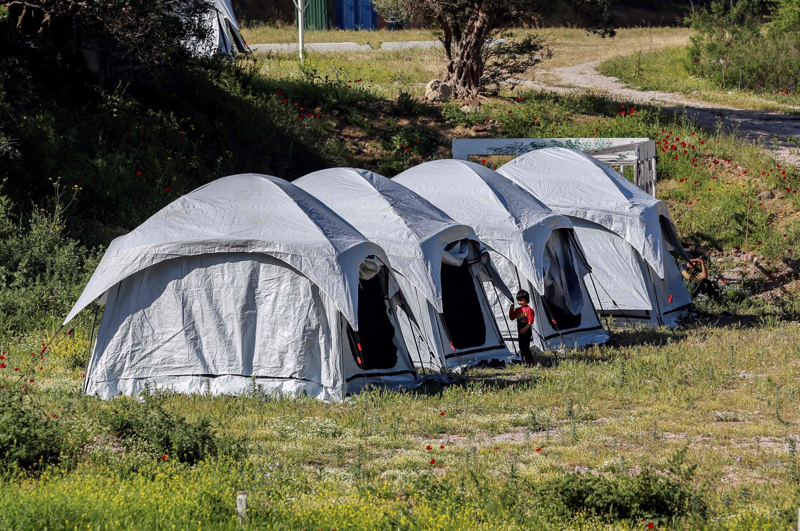 Children play outside the tents at a migrant and refugee camp where cases affected by the COVID-19 were detected, on the Greek mediterranean island of Lesbos, May 13, 2020. (AFP)
