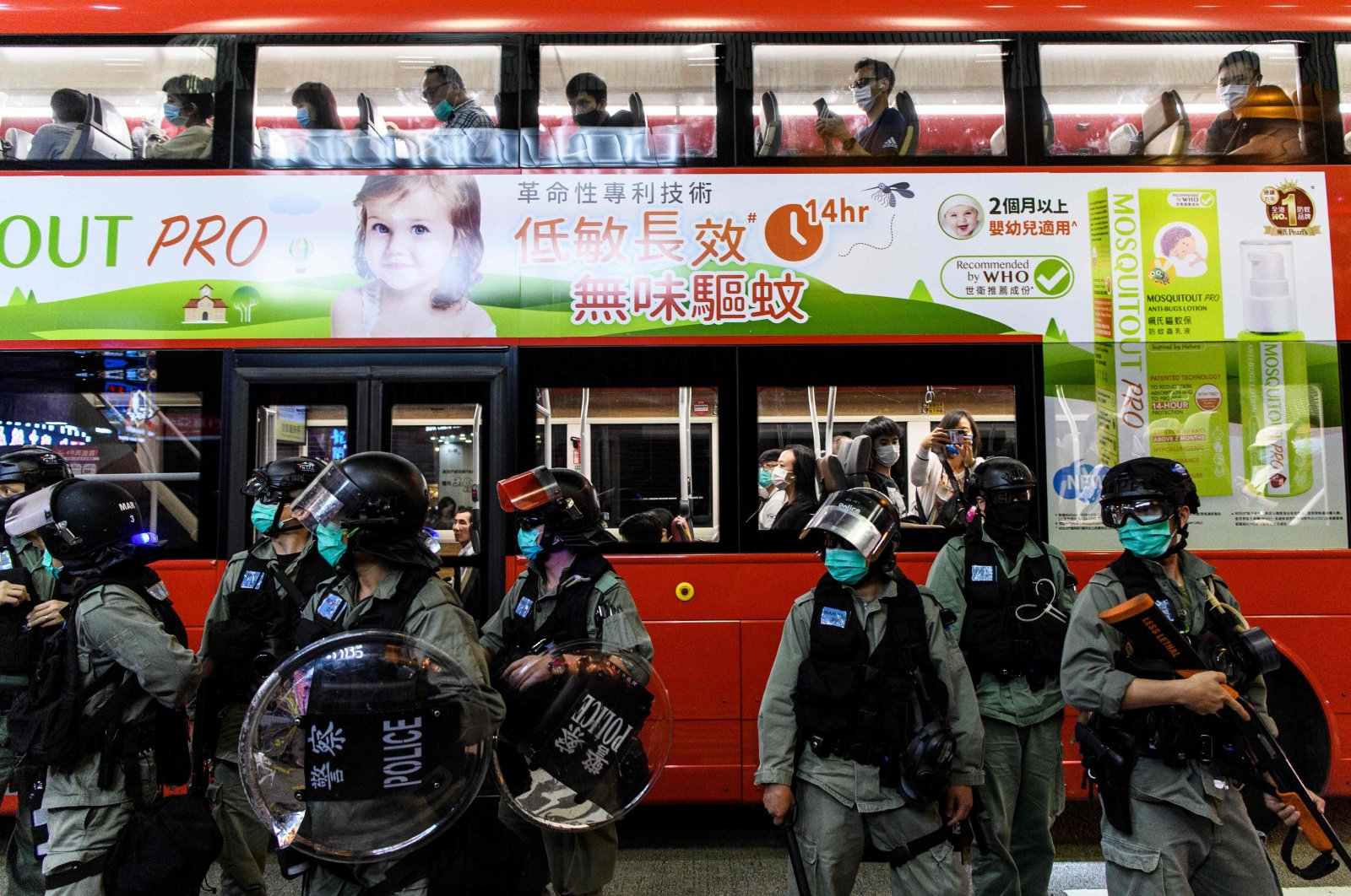 Commuters are driven past a group of riot police on a street after an anti-government protest took place in a shopping mall, Hong Kong, May 13, 2020. (AFP Photo)