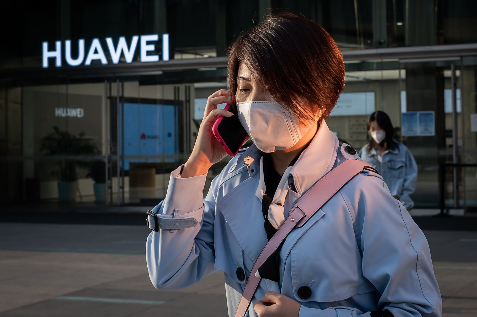 A woman wearing a mask speaks on her phone outside a Huawei shop in Beijing, China, April 1, 2020. (AFP Photo)
