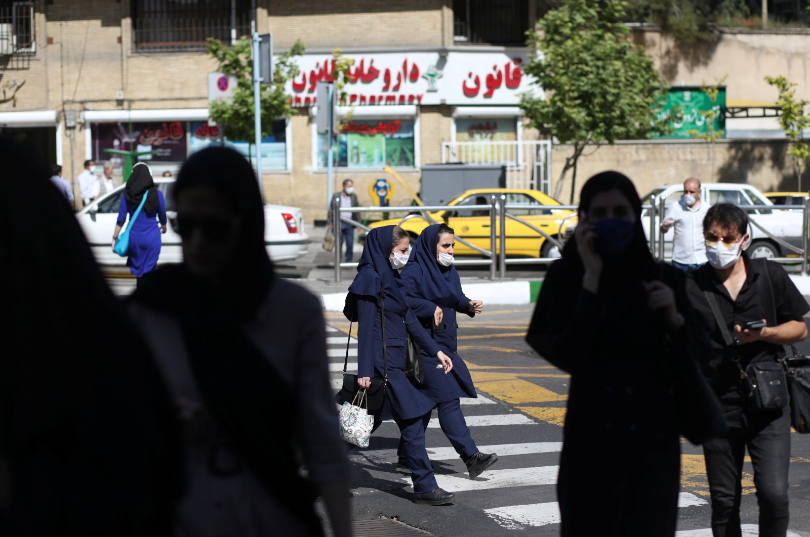 Iranians wear protective face masks and gloves, following the outbreak of the coronavirus disease (COVID-19), as they walk in Vali-E-Asr street, in Tehran, Iran, May 12, 2020. (Reuters Photo)