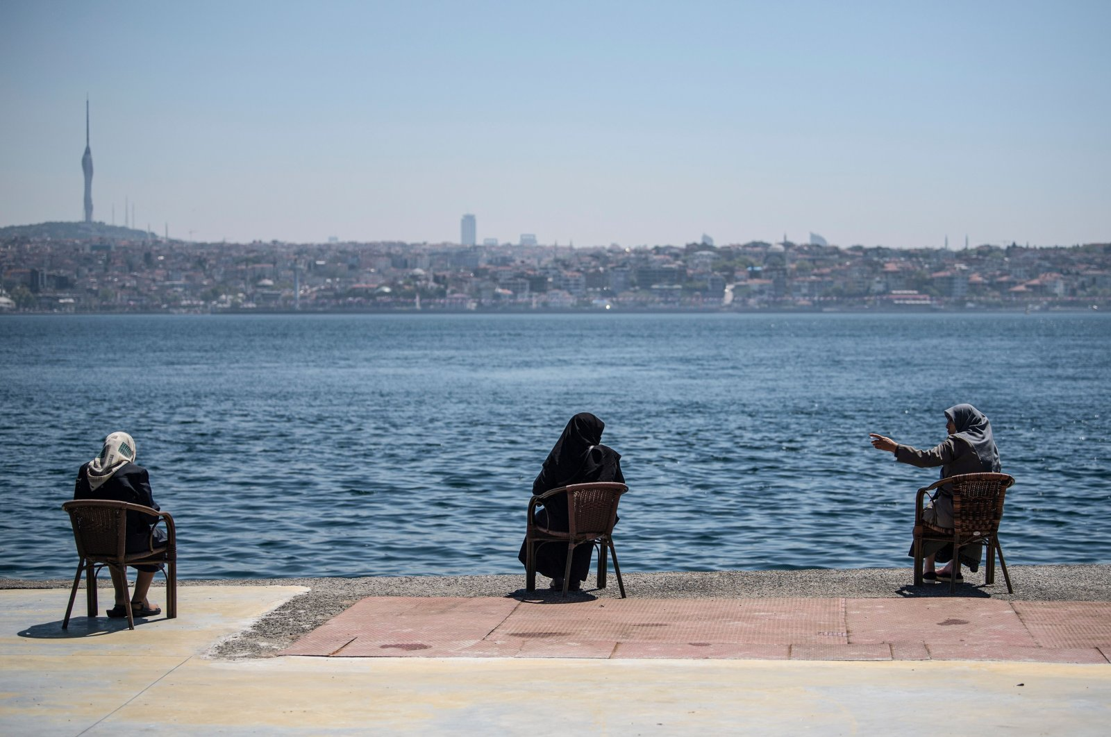 Women wearing protective face masks sit apart following social distancing measures at the seaside overlooking the Bosporus in Istanbul, Turkey, May 10, 2020. (AP Photo)