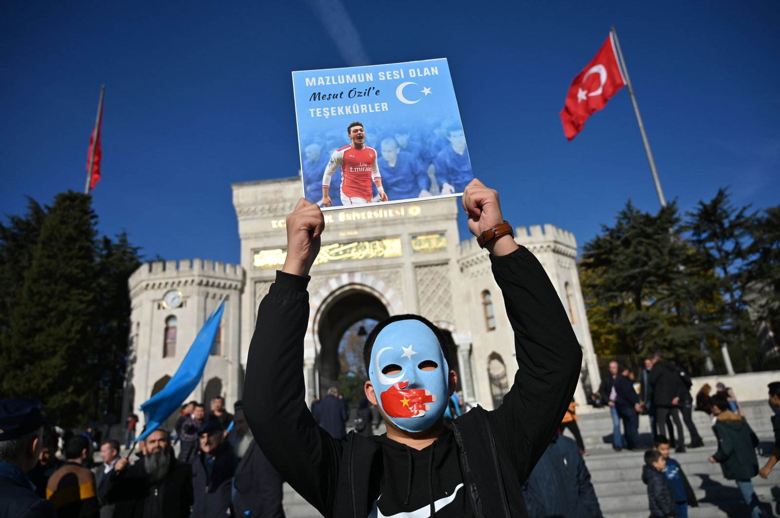"""In this file photo taken on December 14, 2019 a supporter of China's Muslim Uighur minority holds a placard of Arsenal's Turkish origin German midfielder Mesut Ozil reading """"Thanks for being our voice"""" during a demonstration at Beyazid square in Istanbul. (AFP Photo)"""