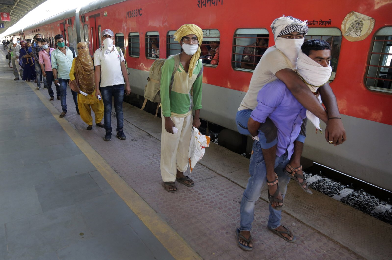 In this Saturday, May 2, 2020, photo, a man carries his physically disabled brother on his back as they wait to board a special train to return to Agra in Uttar Pradesh state, during a nationwide lockdown to curb the spread of new coronavirus, at a railway station in Ahmedabad, in the western Indian state of Gujarat. (AP Photo)