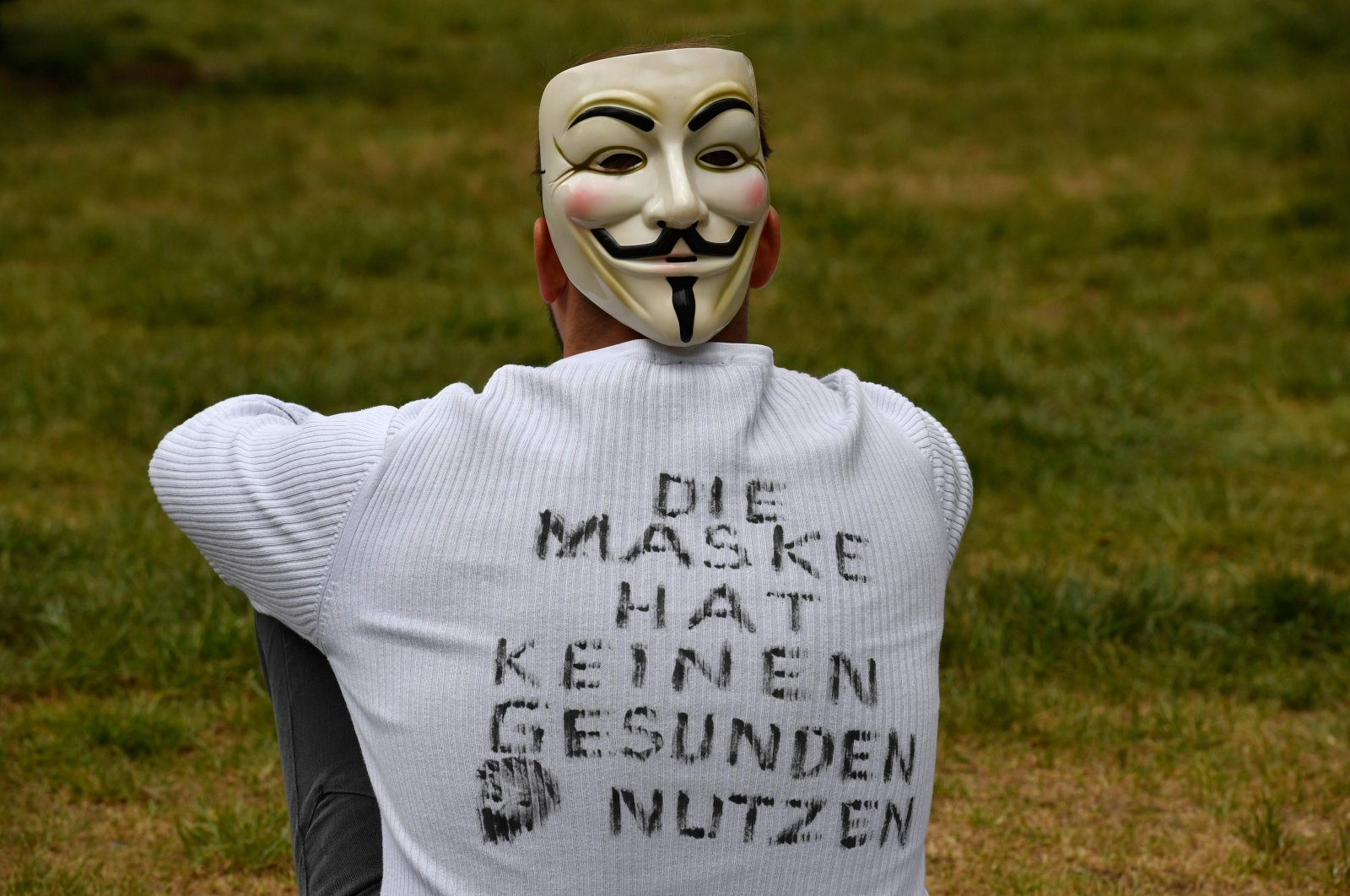 A demonstrator wearing a mask and a T-shirt with inscriptions reading 'The mask has no healthy use' sits in the demo area during a protest against the coronavirus-related restrictions in Berlin, May 2, 2020. (AFP Photo)