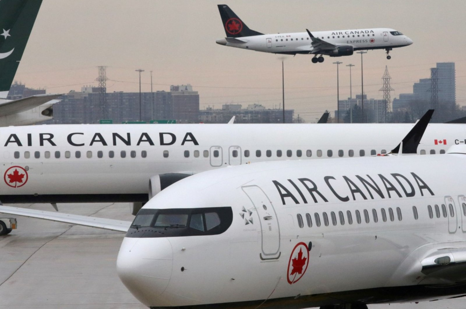Two Air Canada Boeing 737 MAX 8 aircrafts are seen on the ground as Air Canada Embraer aircraft flies in the background at Toronto Pearson International Airport in Toronto, Ontario, Canada, March 13, 2019. (REUTERS Photo)