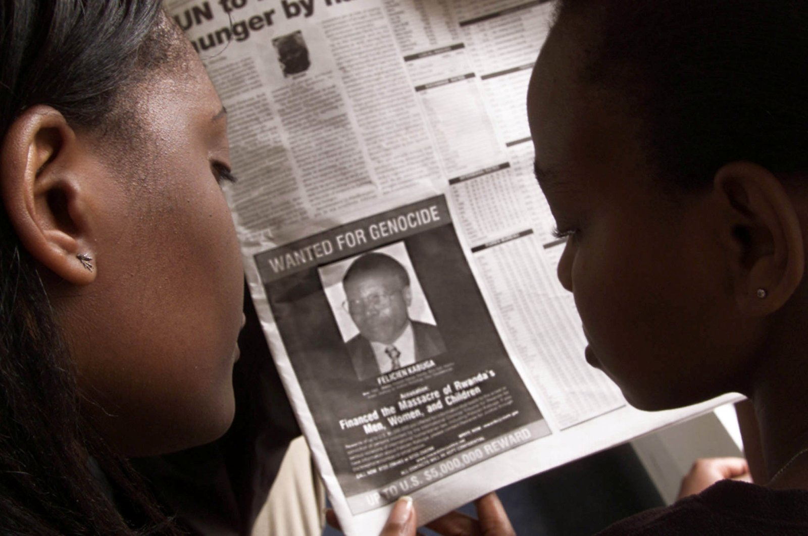 This June 12, 2002, file photo shows readers look at a newspaper carrying the photograph of Rwandan Felicien Kabuga wanted by the United States, in Nairobi, Kenya. (Reuters Photo)