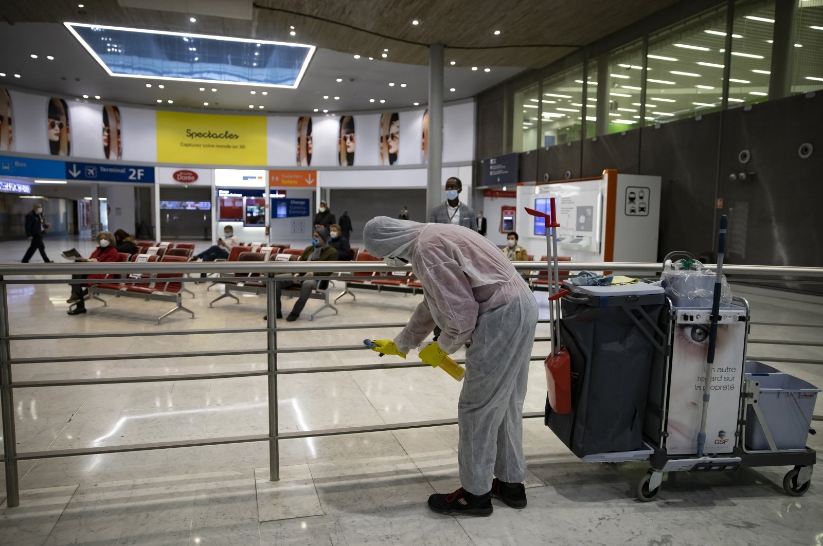 A cleaning personnel disinfects surfaces at Terminal 2 of Charles de Gaulle international airport in Roissy, north of Paris, Thursday, May 14, 2020. (AP Photo)