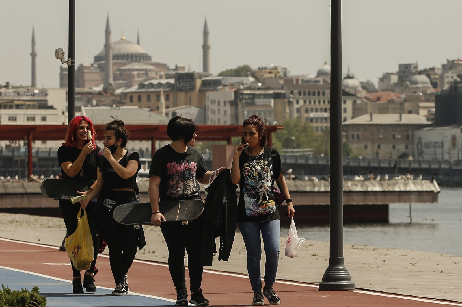 Turkish girls walk in Istanbul, backdropped by the Hagia Sophia as teenagers were able to leave their homes for the first time in 42 days on Friday, as their turn came for a few hours of respite from Turkey's coronavirus lockdowns, Istanbul, Turkey, May 15, 2020. (AP Photo)