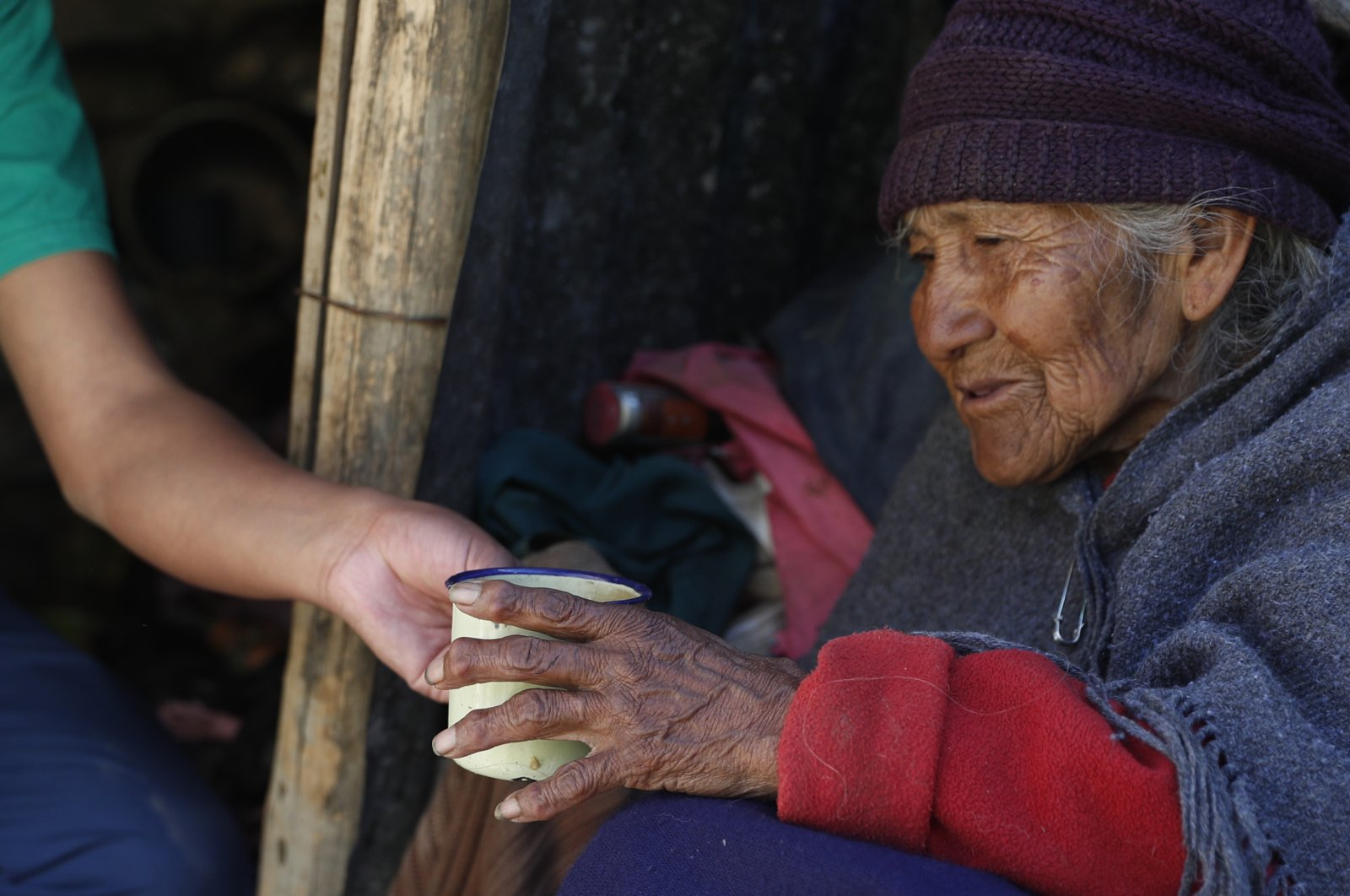 """80-year-old Dominga Aduviri is handed a cup of soda from her """"adopted"""" grandson Wilmer Gutierrez, in La Paz, Bolivia, May 11, 2020. (AP Photo)"""