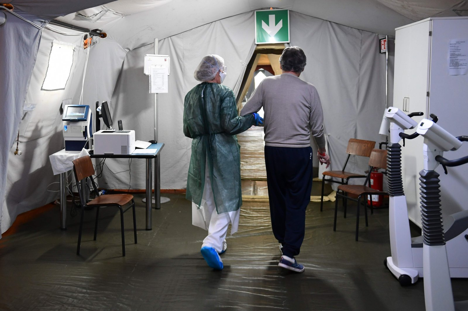 A nurse helps a patient who recovered from COVID-19 walk in a former COVID-19 patient rehabilitation center inside the field hospital in Crema, southeast of Milan, on May 15, 2020.(AFP Photo)