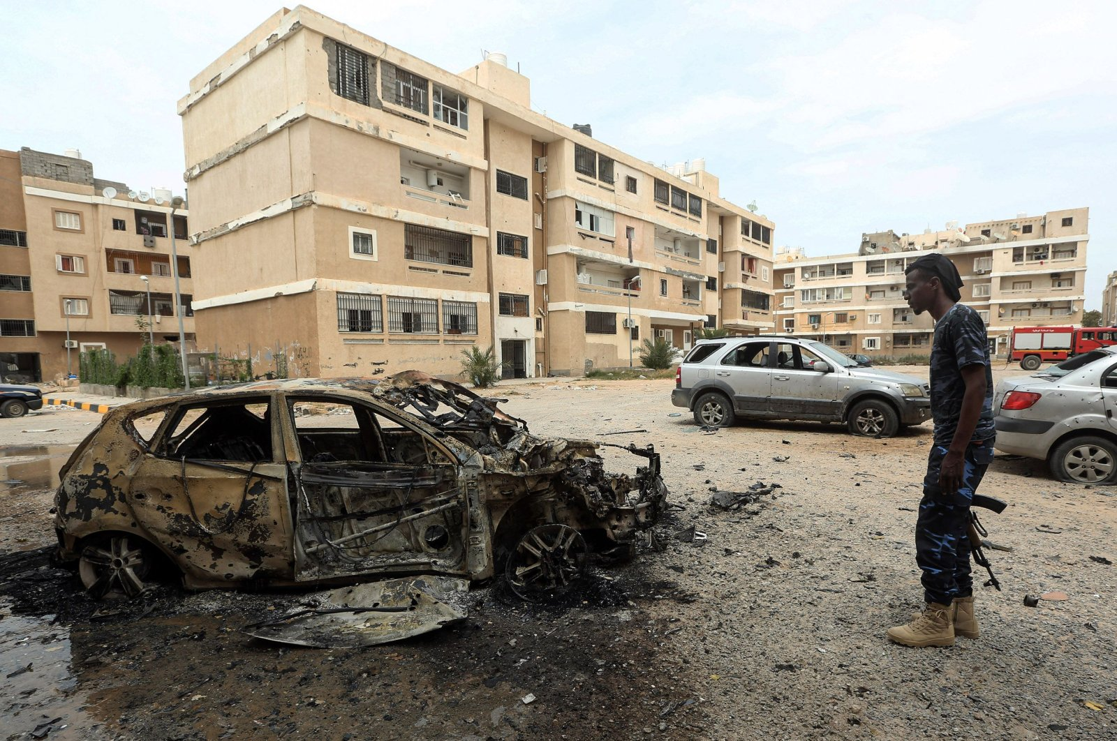 A fighter loyal to Libya's U.N.-recognized Government of National Accord (GNA) stands next to a destroyed car following bombardment in the residential Bab Bin Ghashir neighborhood of Libya's capital Tripoli on May 9, 2020.