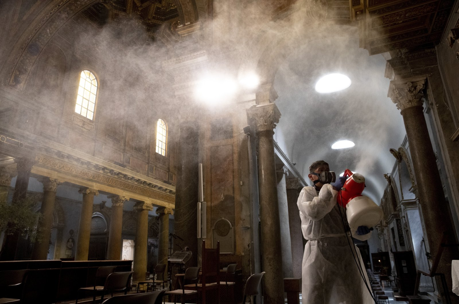 A man sprays disinfectant as he sanitizes Santa Maria in Trastevere Basilica to prevent the spread of the COVID-19 coronavirus, in Rome, May 13, 2020. (AP Photo)
