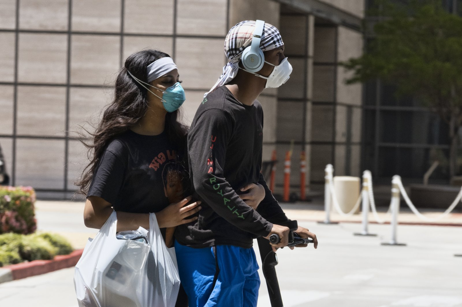 A couple wearing protective masks from the coronavirus ride a scooter down the street past the Ronald Reagan UCLA Medical Center in the Westwood section of Los Angeles, California, U.S. on May 15, 2020. (AP Photo)