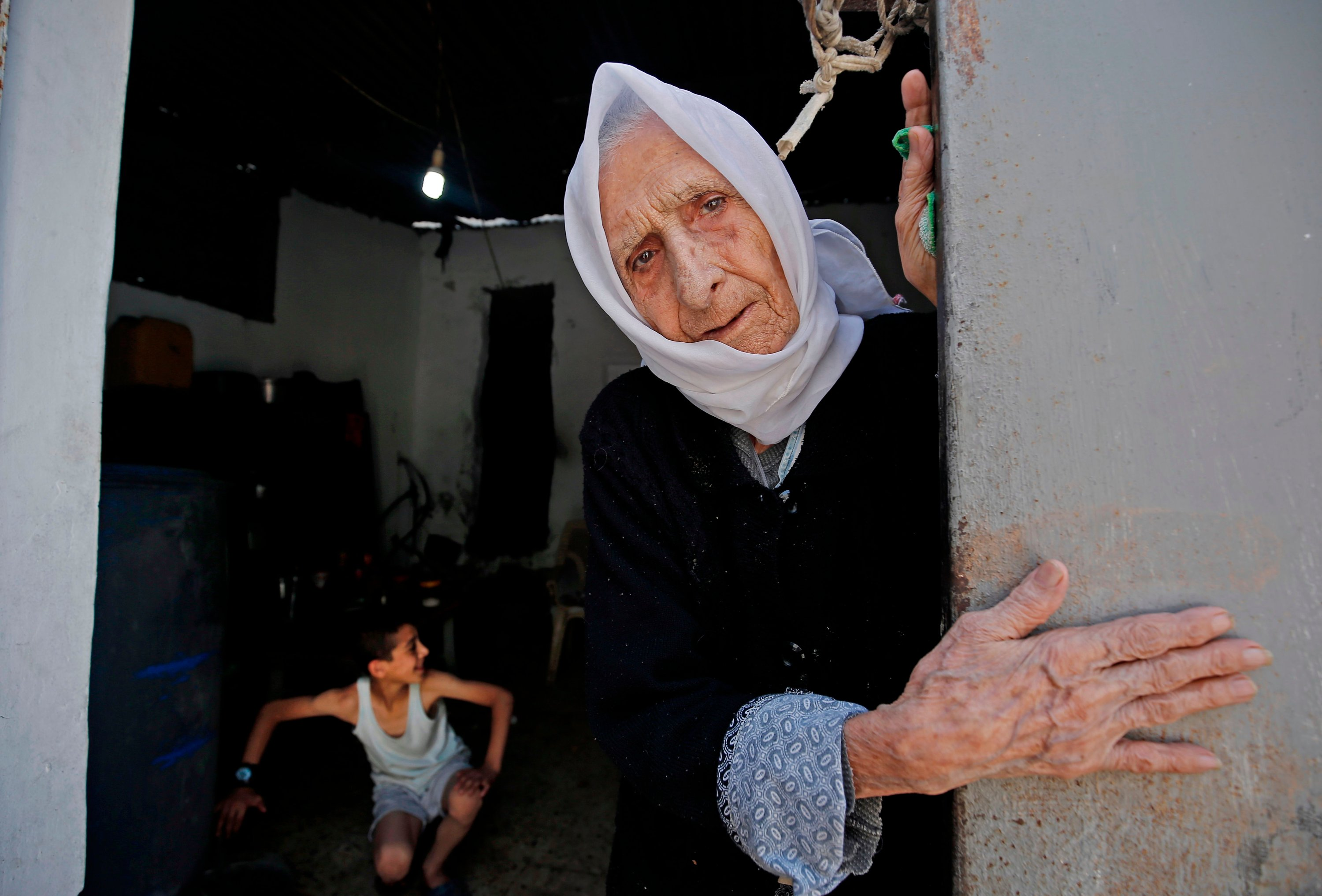 A Palestinian refugee elderly woman, who witnessed the 1948 Nakba, looks out of her house's entrance door at Al-Shati refugee camp in Gaza City, May 15, 2020. (AFP)