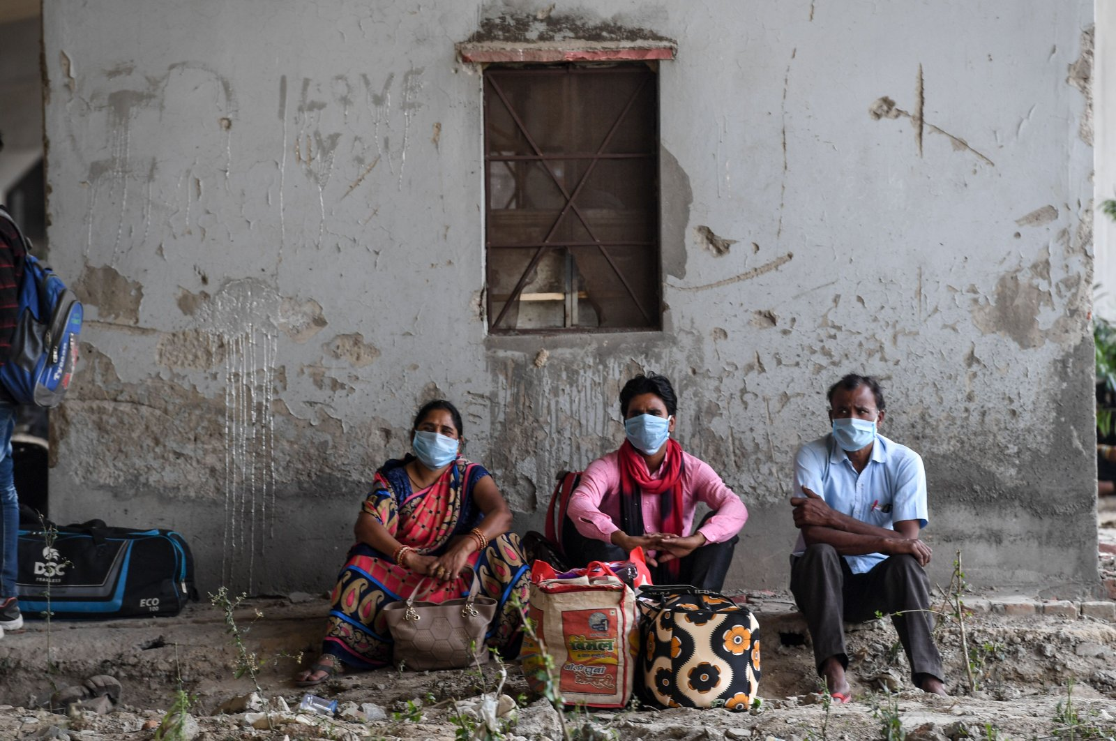 Migrant workers and families wait for transport to go to their hometowns in Uttar Pradesh and Bihar states after police stopped them from crossing the Delhi-Uttar Pradesh states border on foot as the government eased a nationwide lockdown as a preventive measure against the COVID-19 coronavirus, New Delhi, May 15, 2020. (AFP Photo)
