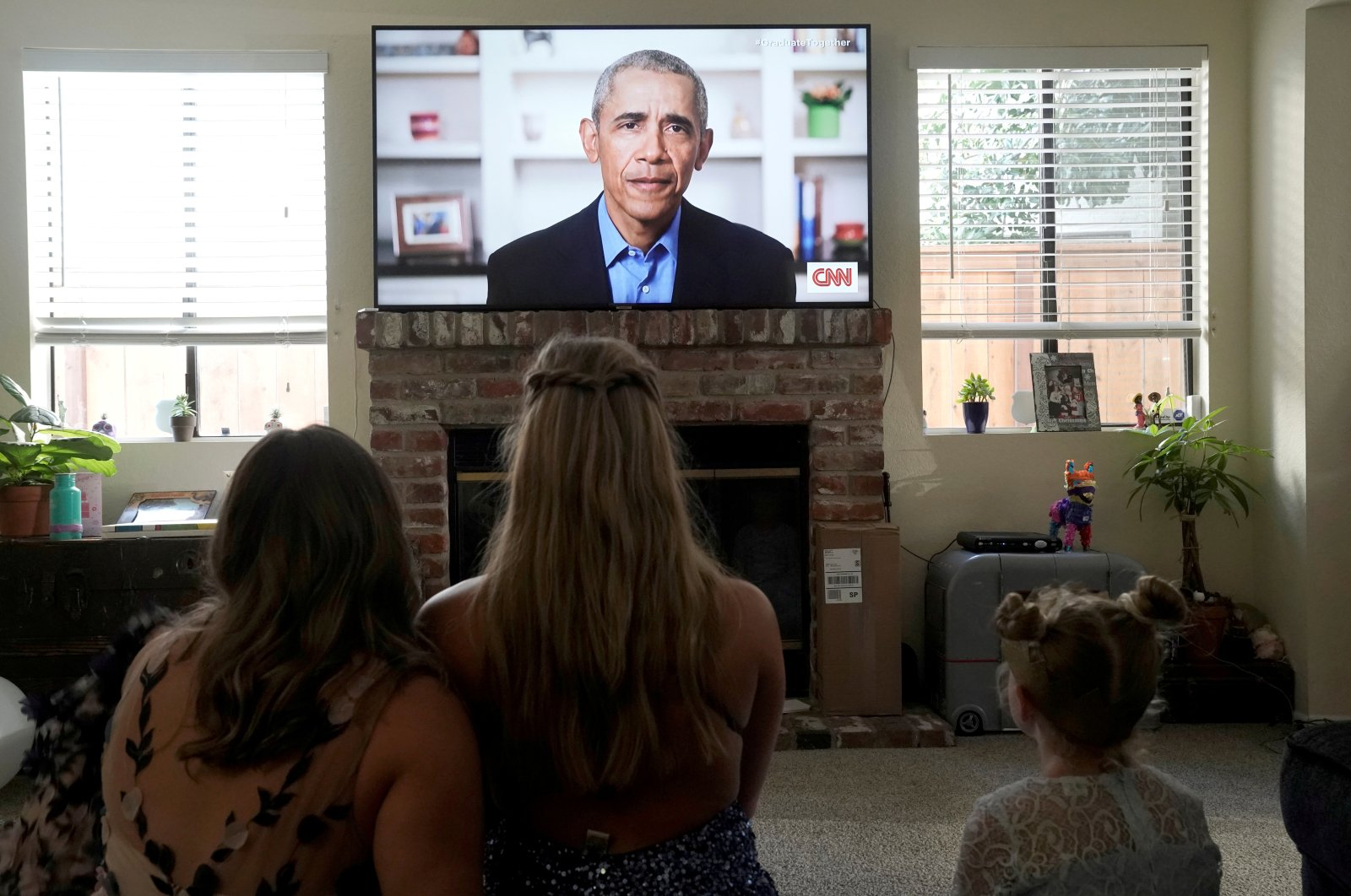 Torrey Pines High School graduating student Phoebe Seip (C), 18, and her sisters Sydney (L), 22, and Paisley, 6, watch former U.S. President Barack Obama deliver a virtual commencement address to millions of high school seniors who will miss graduation ceremonies due to the COVID-19 outbreak, while celebrating Phoebe's canceled prom night at home in San Diego, California, U.S., May 16, 2020. (Reuters Photo)