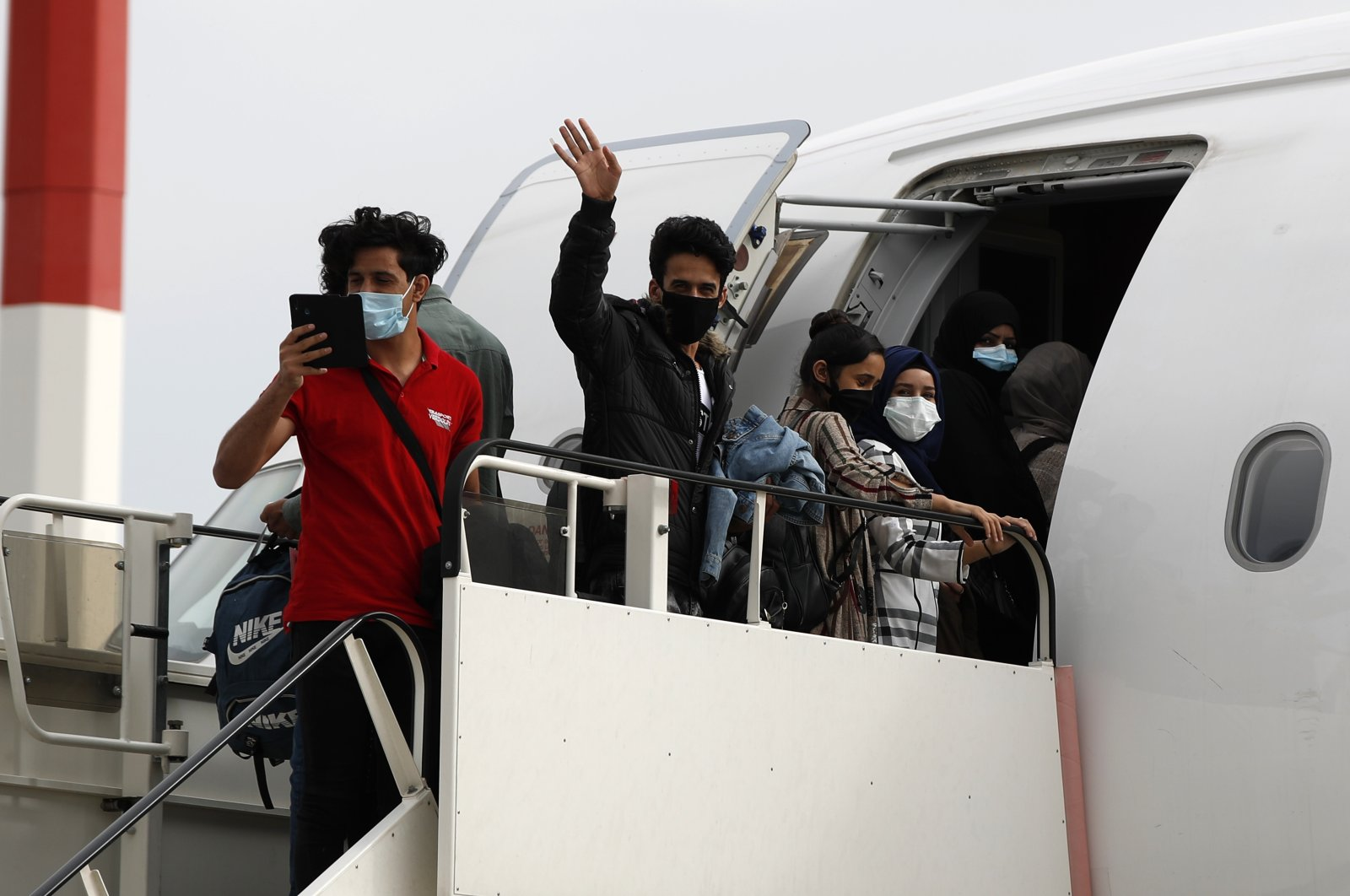Migrants wearing face masks to prevent the spread of the coronavirus, board an airplane bound for Britain at the Eleftherios Venizelos International Airport in Athens, May 11, 2020. (AP)
