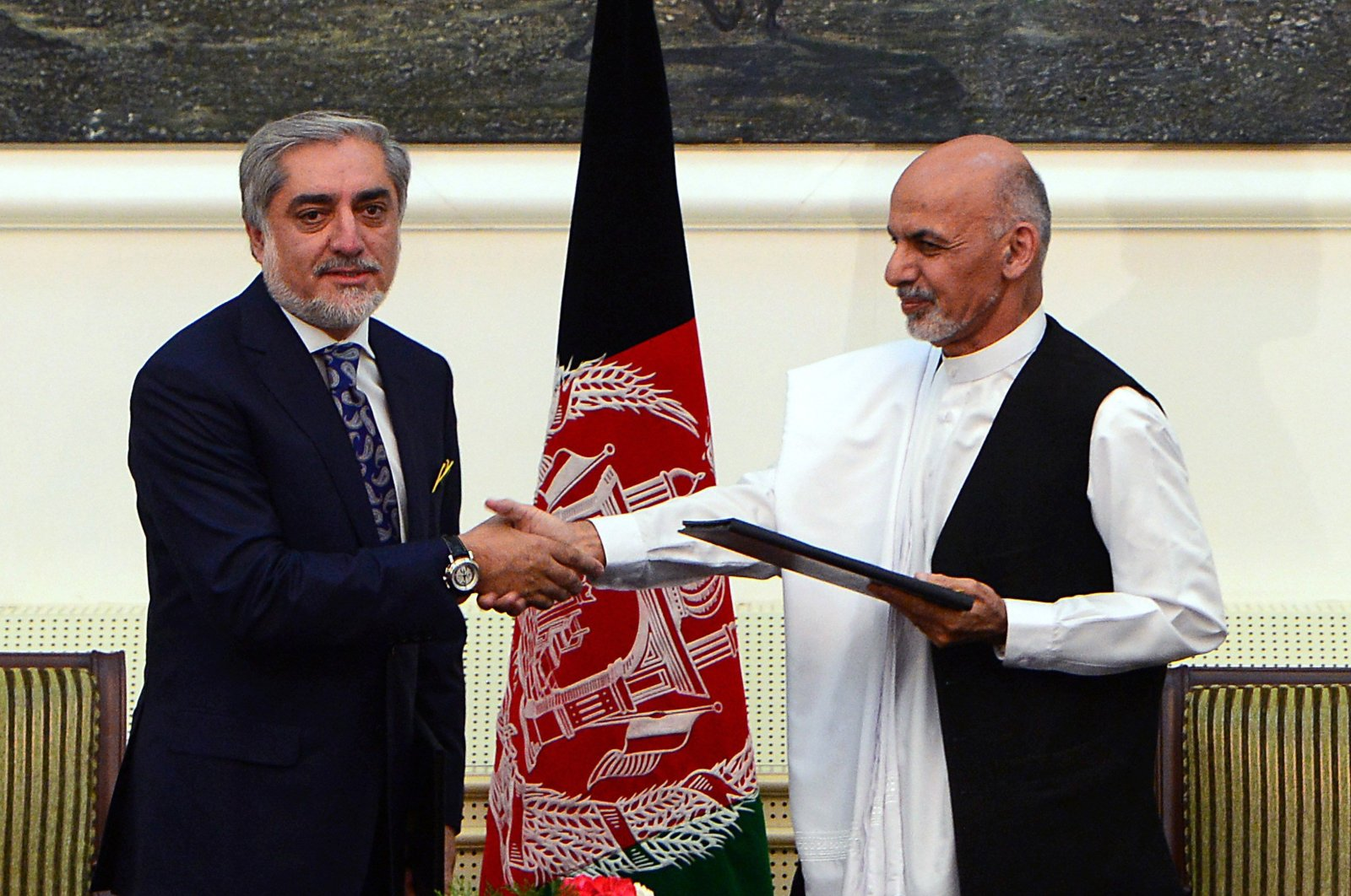 In this file photo, Afghan presidential candidates Abdullah Abdullah (L) and Ashraf Ghani Ahmadzai shake hands after signing a power-sharing agreement at the Presidential Palace in Kabul on Sept. 21, 2014. (AFP Photo)