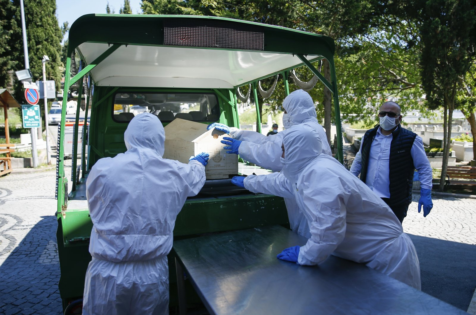 Morgue technicians wearing protective suits load the coffin of a woman who died of COVID-19 onto a hearse, Istanbul, Turkey, May 10, 2020. (AP Photo)