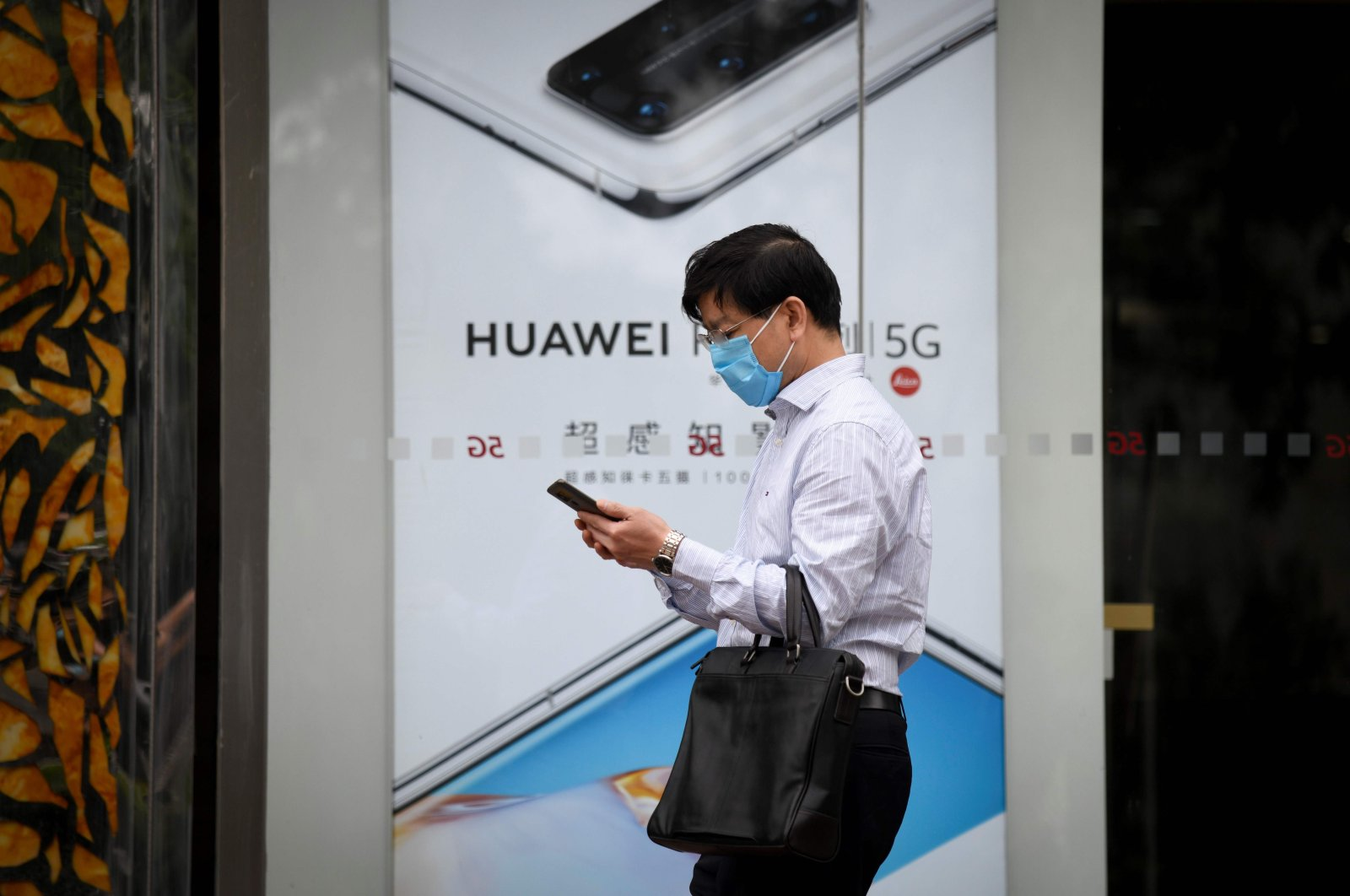 A man wearing a face mask uses his mobile phone as he walks past a poster of Huawei P40 in Beijing, May 16, 2020. (AFP Photo)