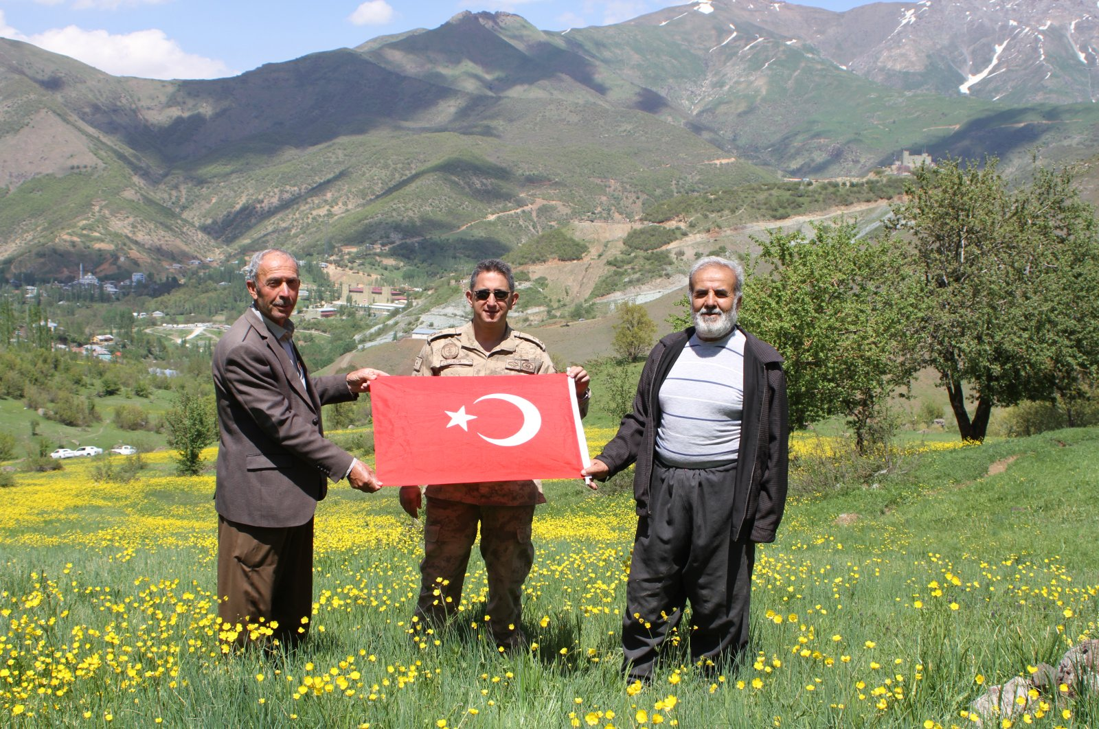 Locals walk in a plateau cleared of the PKK terrorist elements with a Turkish flag at hand, Hakkari, May 17, 2020. (AA)