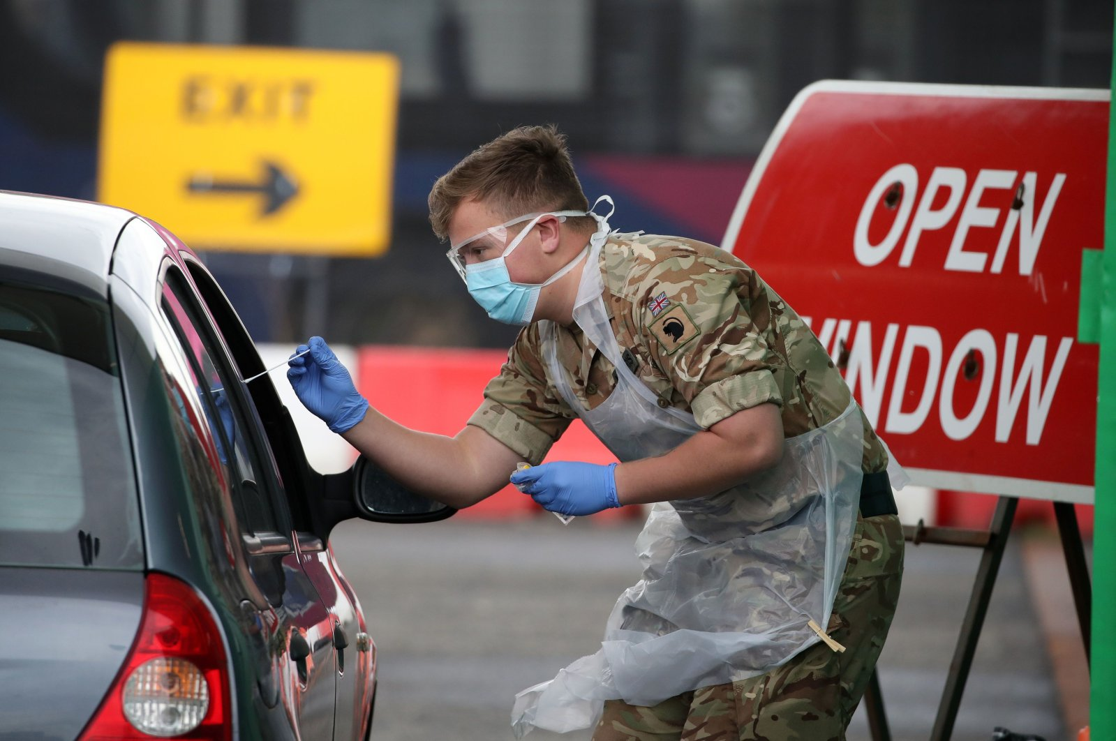 A soldier from 2 Scots Royal Regiment of Scotland tests a key worker for the coronavirus at a drive-in testing center at Glasgow Airport, U.K., April 29, 2020. (AFP Photo)