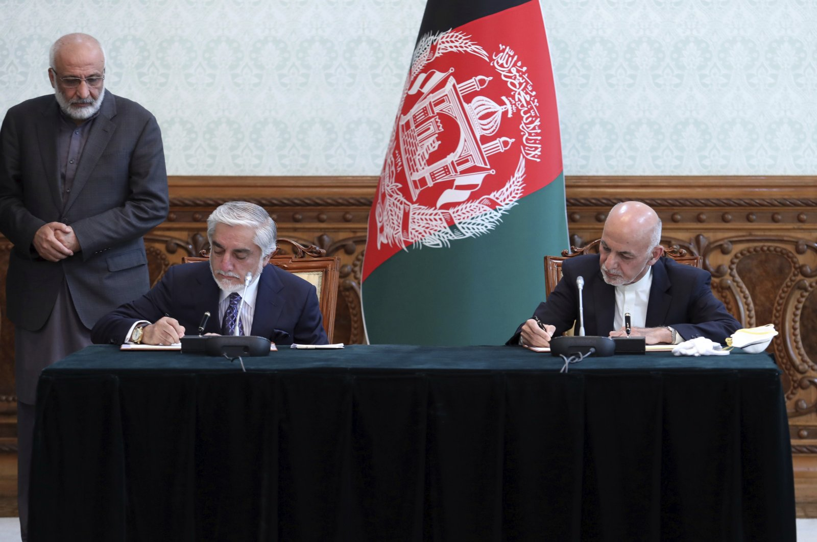 Afghan President Ashraf Ghani, right, and political rival Abdullah Abdullah sign a power-sharing agreement at the presidential palace in Kabul, Afghanistan, Sunday, May 17, 2020. Afghanistan. (AP Photo)