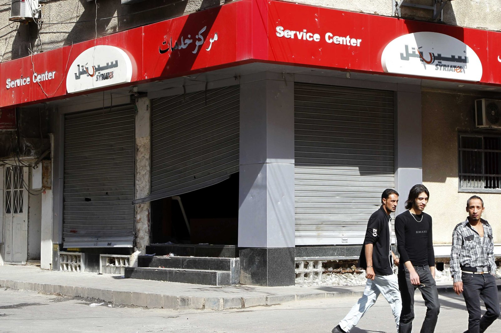People walk past the looted premises of cellphone company Syriatel, which is owned by Rami Makhlouf, the cousin of Syrian dictator Bashar Assad, in Daraa, Syria, March 21, 2011. (Reuters Photo)