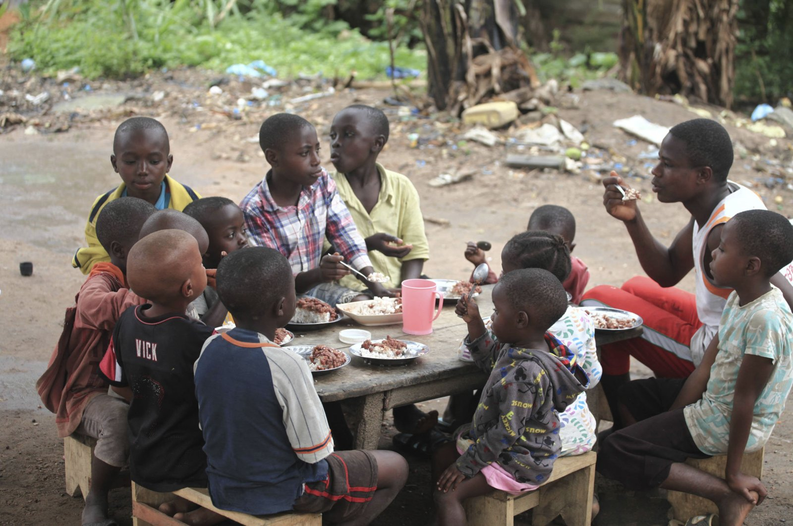 Children orphaned in attacks by rebel groups eat under a tree after being taken in by a local woman, in eastern Democratic Republic of Congo, June 4, 2018. (AP Photo)